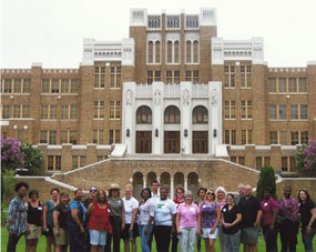Educator's Institute participants standing with a ranger in front of Little Rock Central High School National Historic Site.   NPS Photo.