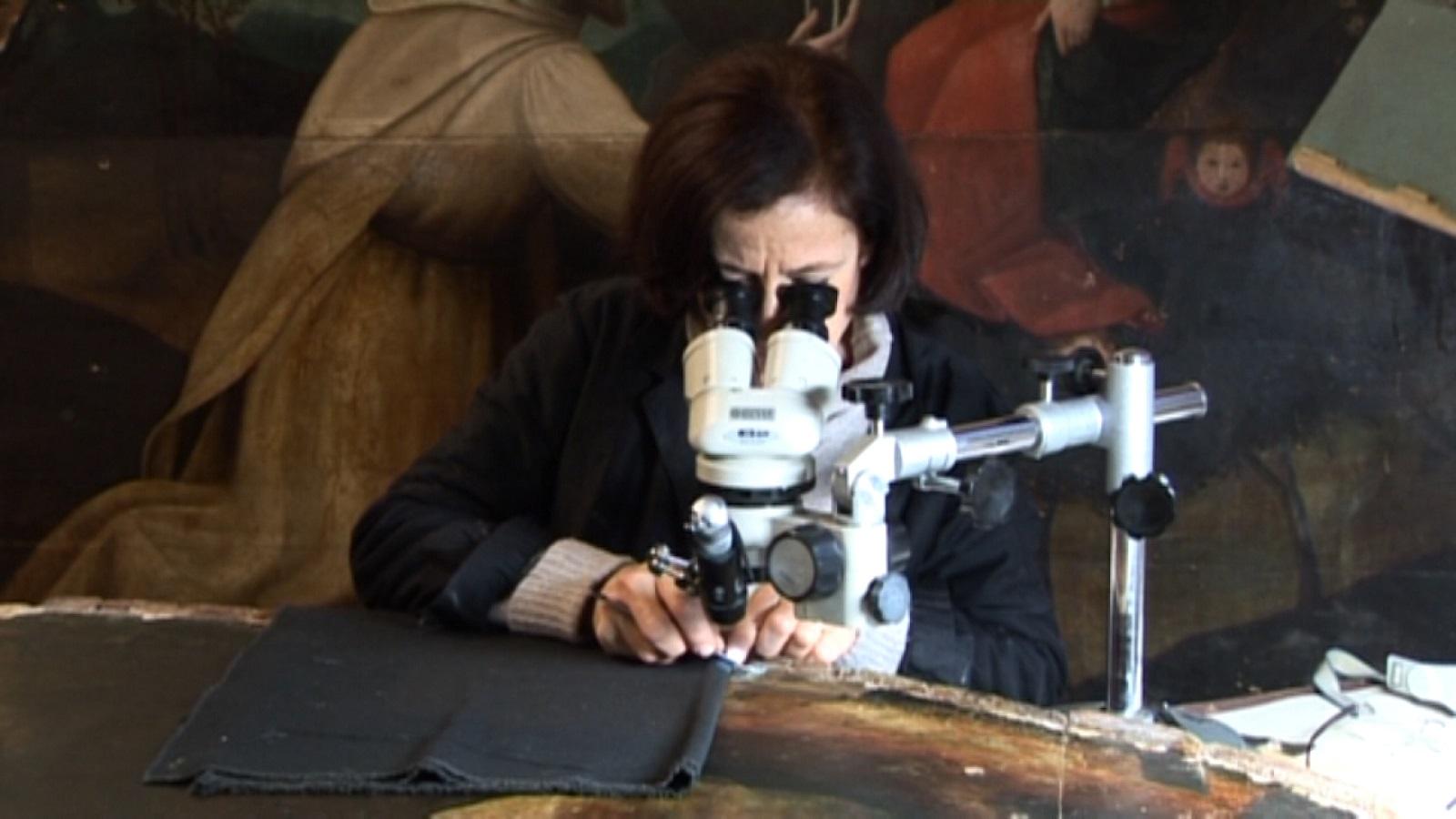 La curatrice Rossella Lari osserva al microscopio il San Domenico di Nelli