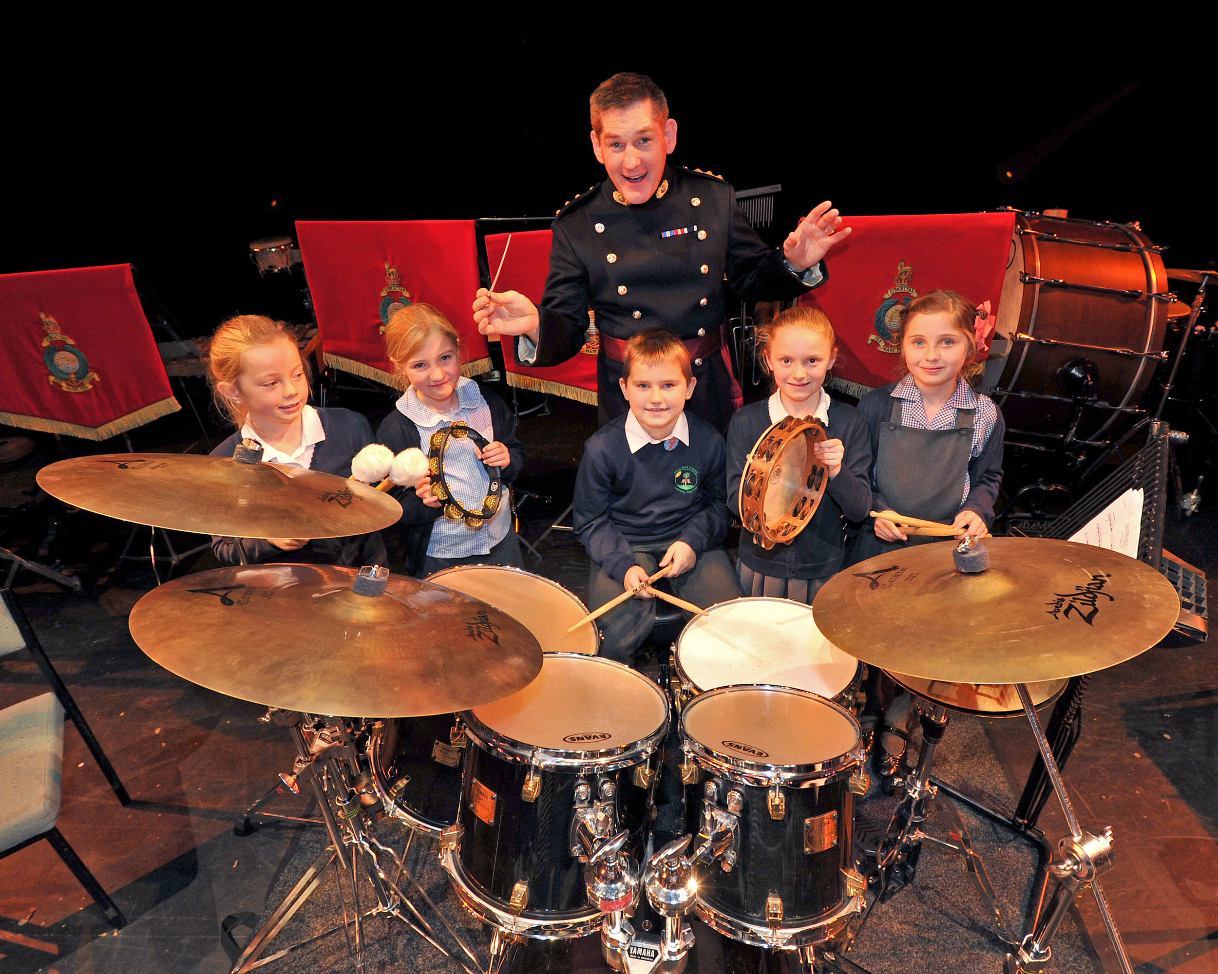 Local school children and Captain Andy Gregory RM from the Royal Marines Band Service
