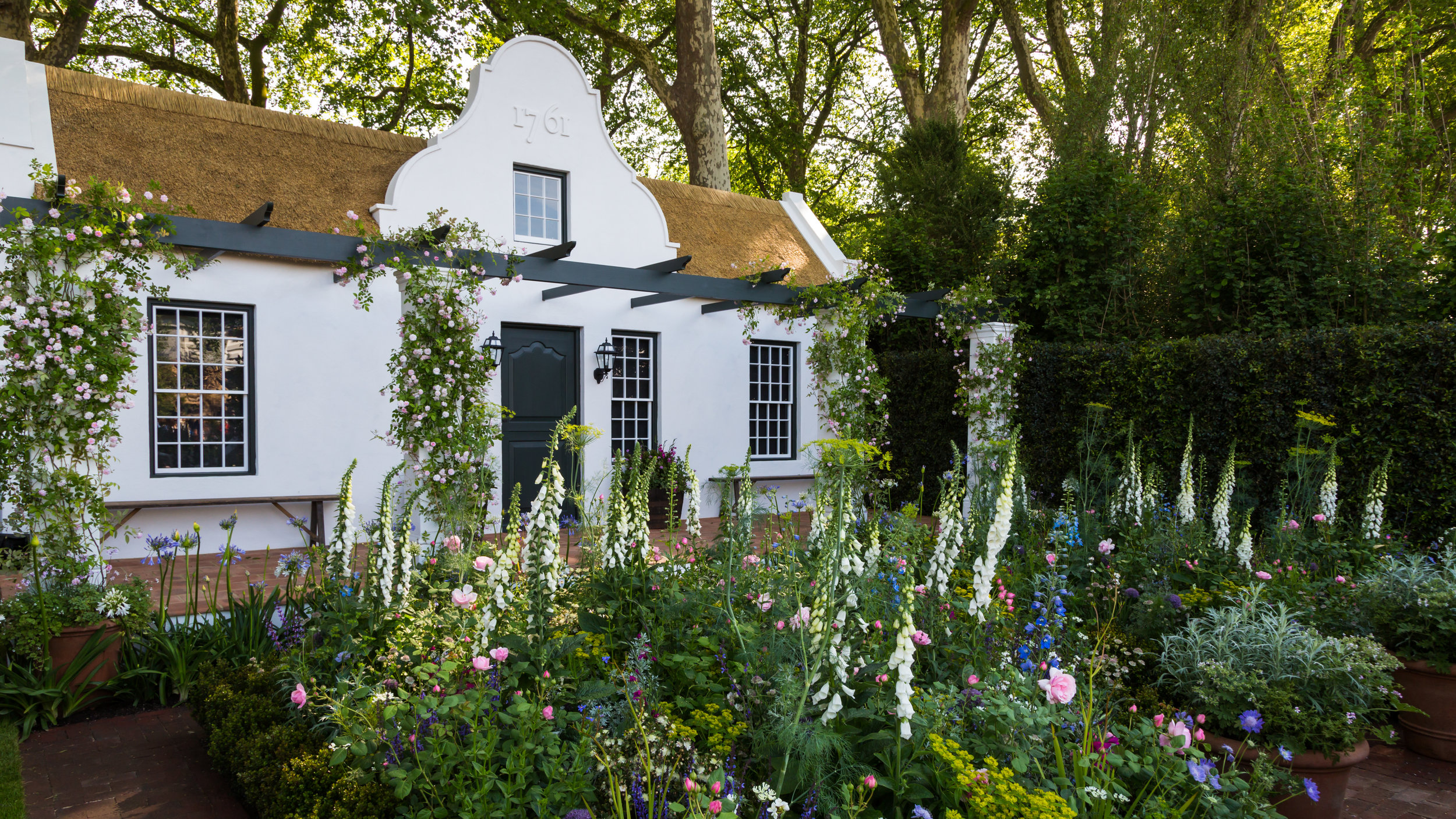 Contrast between the rounded form of the roses and the tall, upright form of the foxgloves is repeated throughout this densely-planted border. Designer:  Jonathan Snow . Image:  Chris Denning/Verve Garden Design.