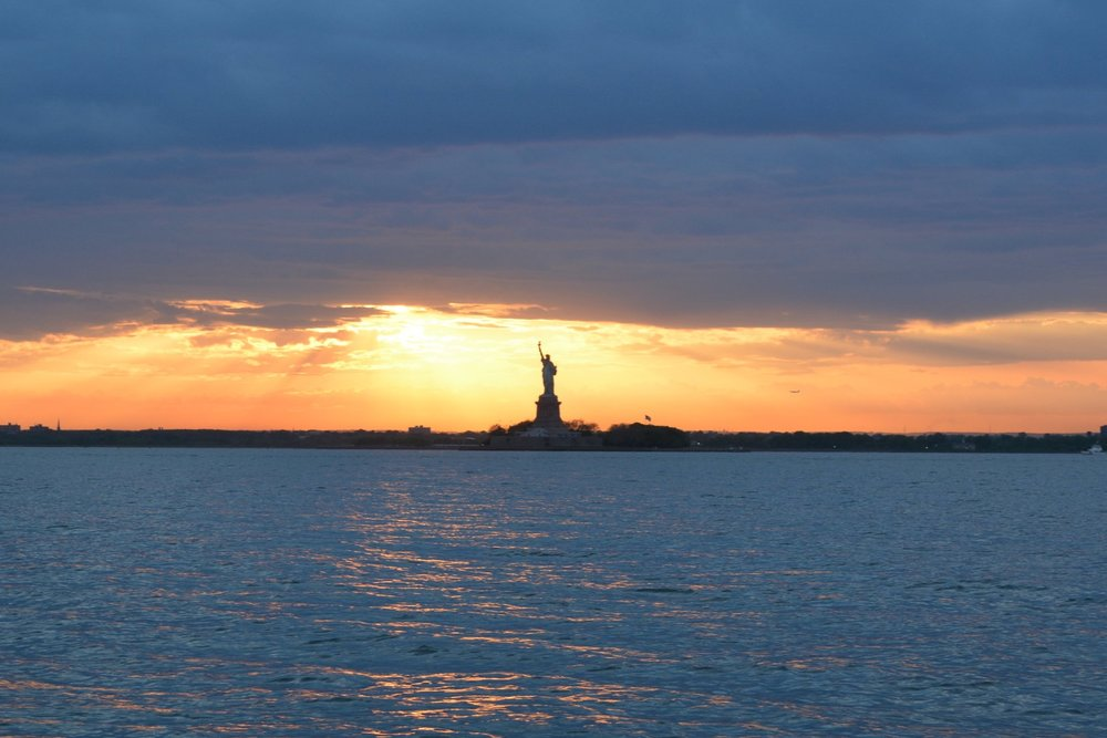 Catch a breathtaking view of the Statue of Liberty at sunset aboard a private tour.