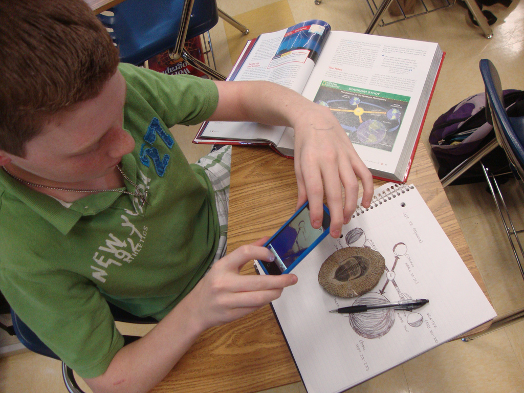 A student looks at a trilobite fossil during an SGS presentation at Caddo Magnet High School.