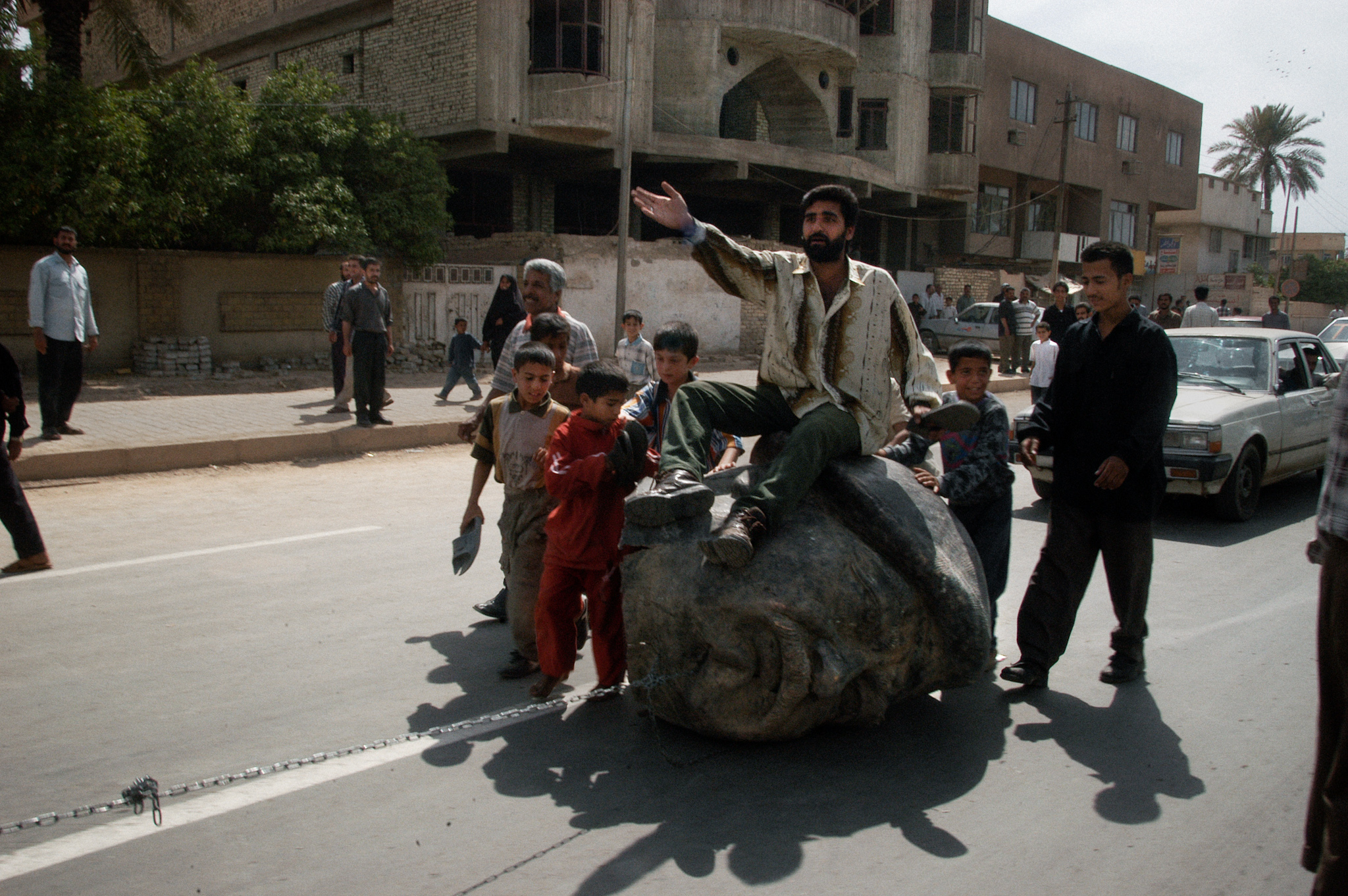 Baghdad, Iraq  April 18, 2003  Iraqis ride a head of Saddam Hussein being dragged by a truck. They are also beating it with shoes, which is considered to be the most insulting gesture in Iraqi society.  Photograph by Alan Chin