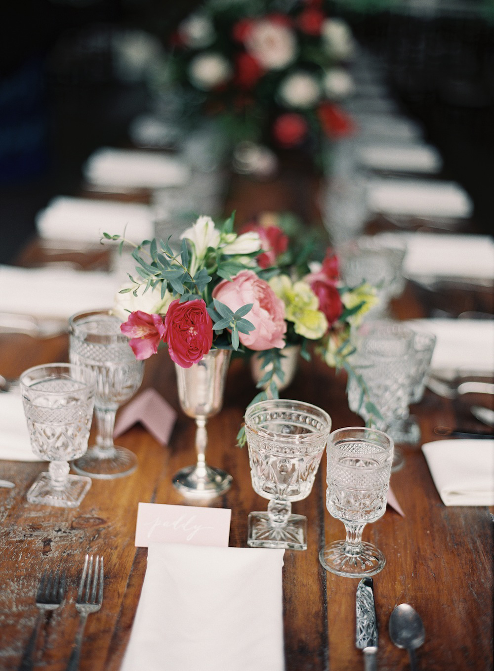 Amazing florals in Southern Vintage silver vessels with our vintage clear pressed wine glasses and water goblets with our silver flatware with beautiful hand lettered place cards equals perfection!