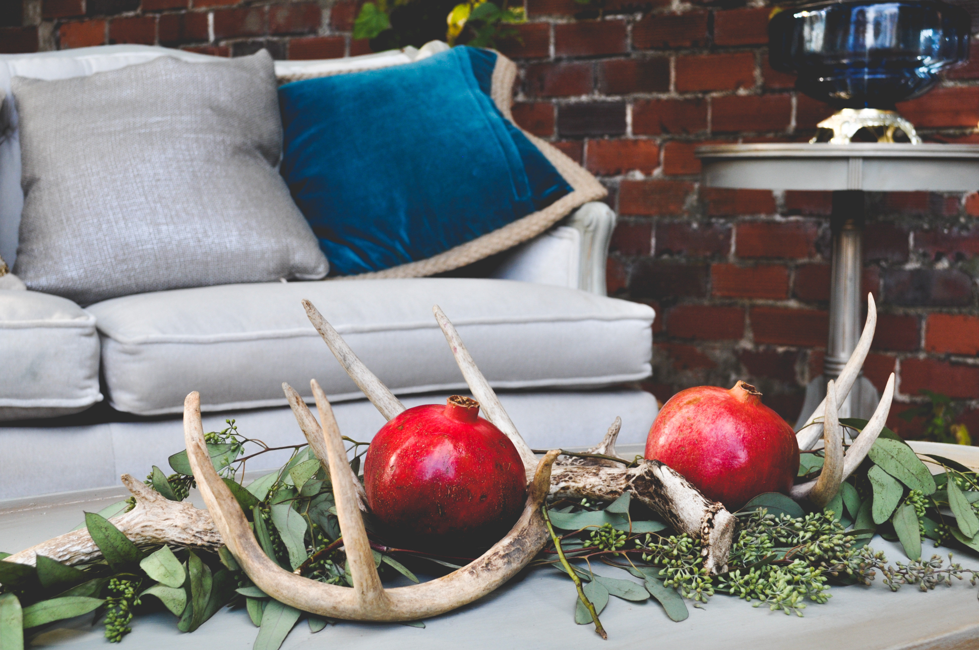 "These ""blood"" pomegranates and antlers add a fall look to this vintage lounge area."