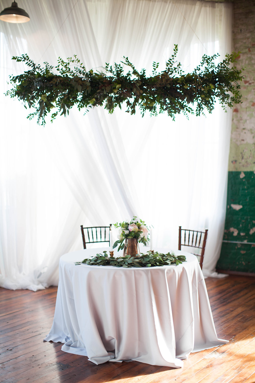 Nothing fussy here! - White draping, minimal beautiful greenery, and TONS of light in an industrial setting. Vintage pieces can be incorporated with all style.