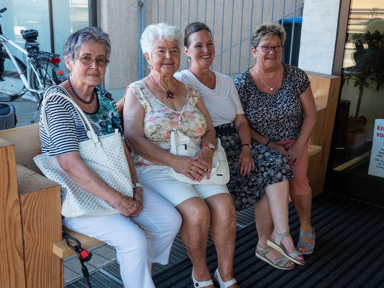 Vier fröhliche Kundinnen erholen sich auf der gespendeten Bank.