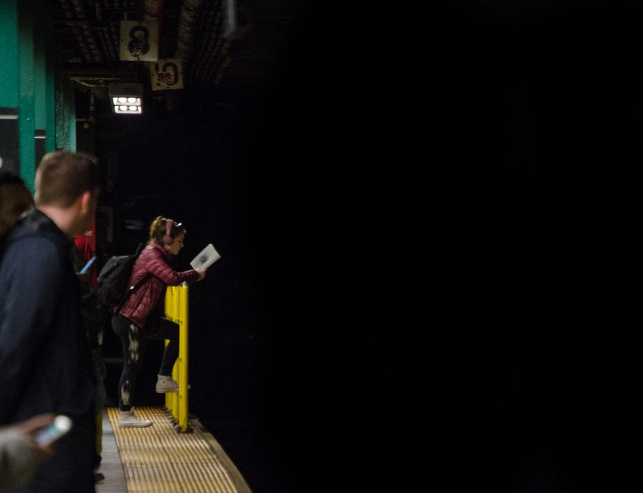 Reading on the platform. Metropolitan Avenue G Train stop. Williamsburg, Brooklyn, NYC.