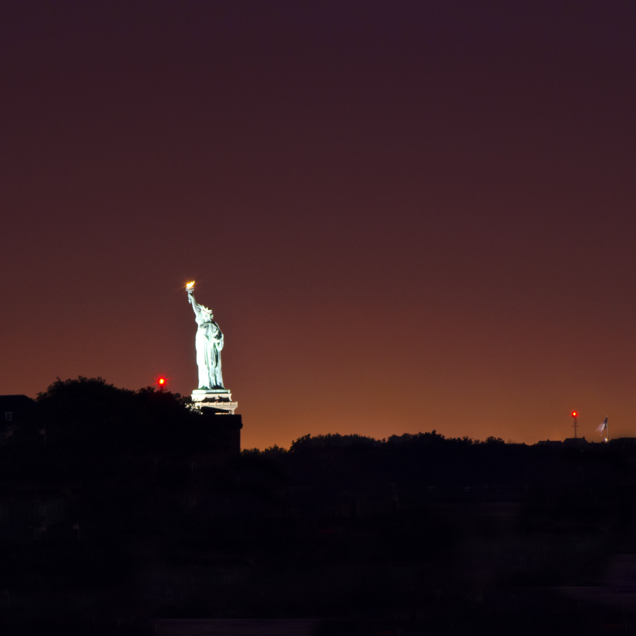 Statue of Liberty at night from a pier in Brooklyn Bridge Park