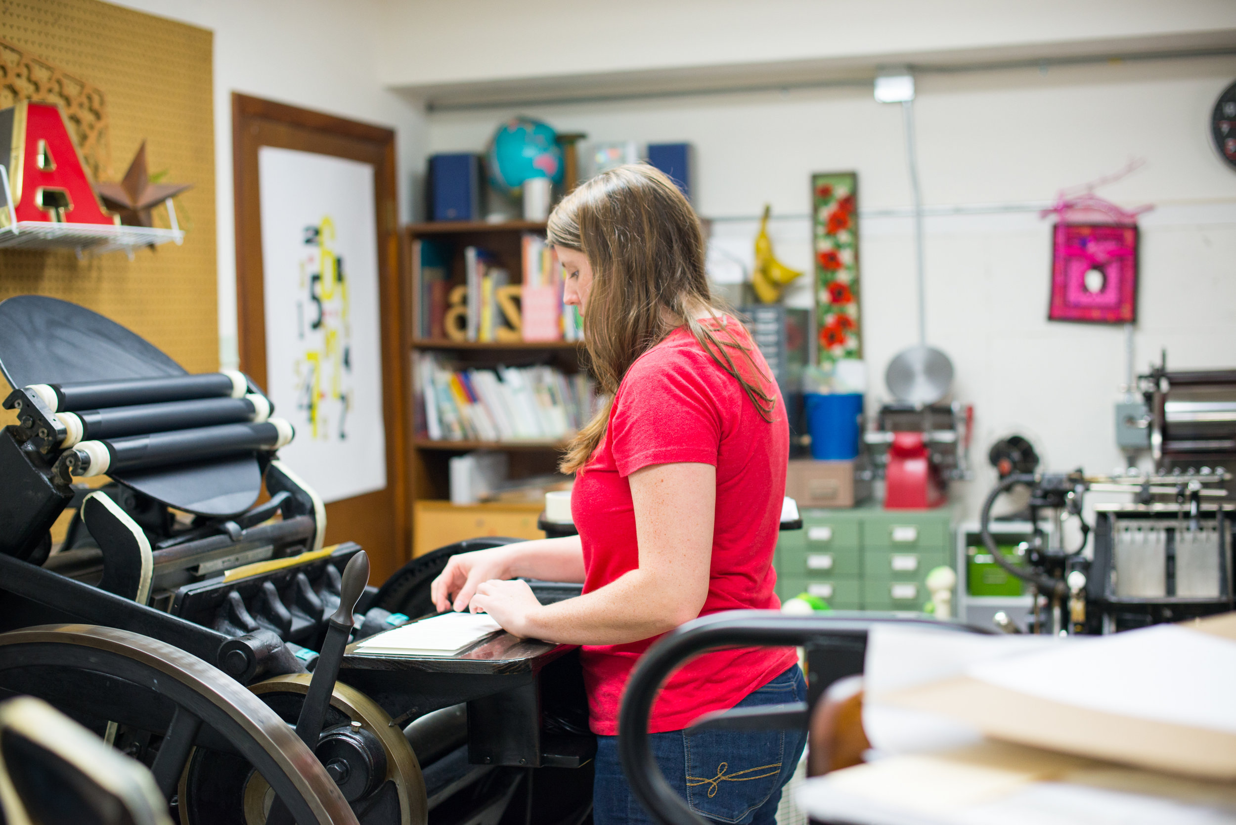 Claire of Hyde & Seek Press works on a printing job for a client. The letterpress printer stands next to the press throughout the entire process and hand-feeds each piece of paper into the press.  LAURA BARNES PHOTO.