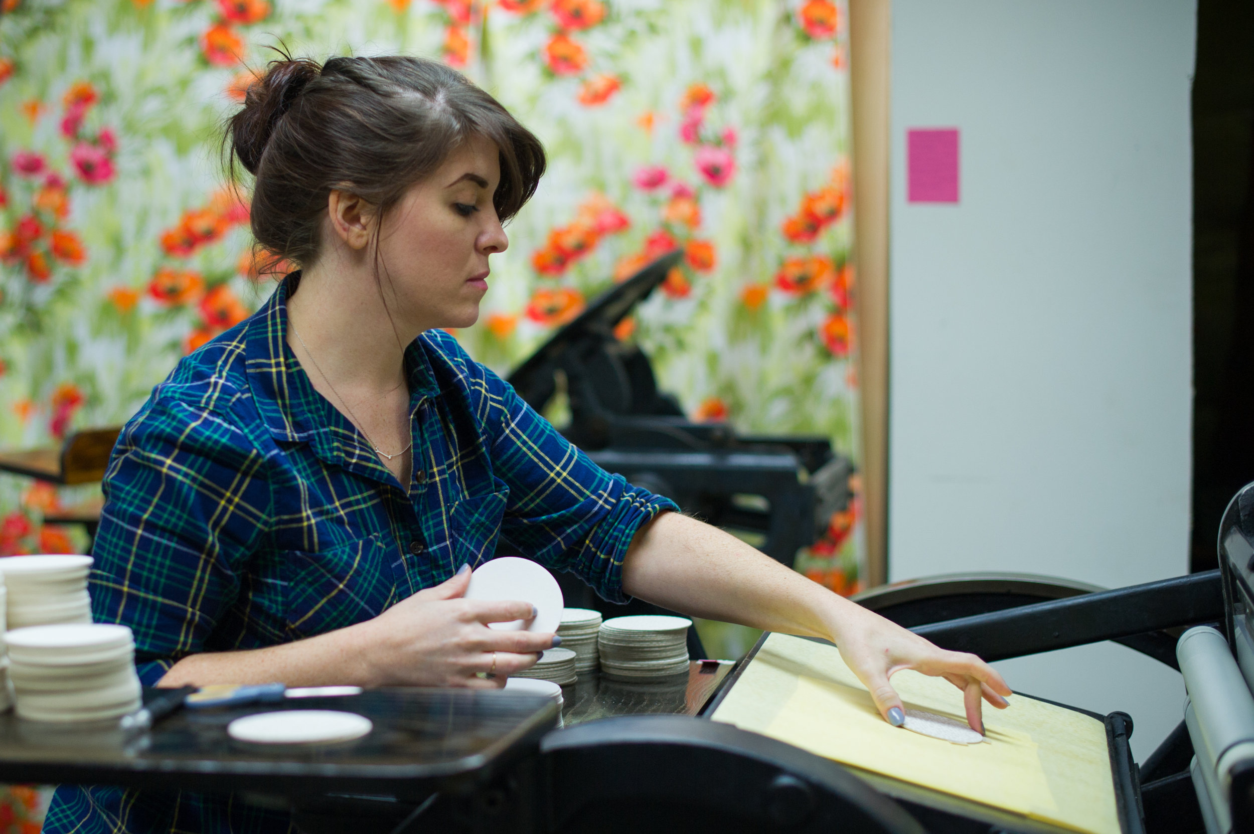 Another press artist feeds round coasters into the press for a special letterpress printing job!  LAURA BARNES PHOTO.