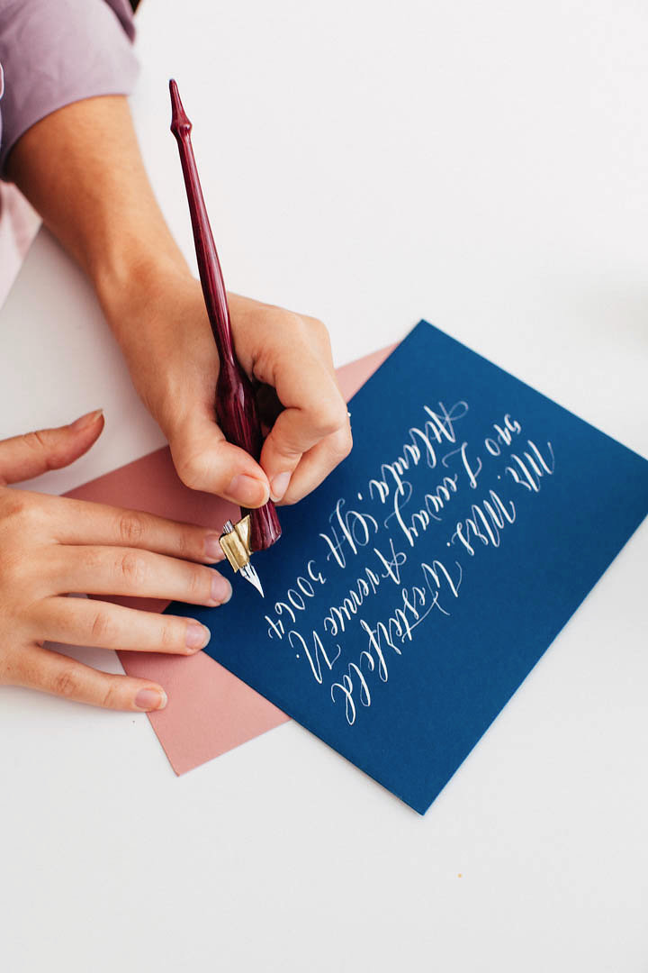 Addressing a navy envelope with white calligraphy! ElisaAnne calligraphy offers 5 main styles of calligraphy for custom wedding invitations.