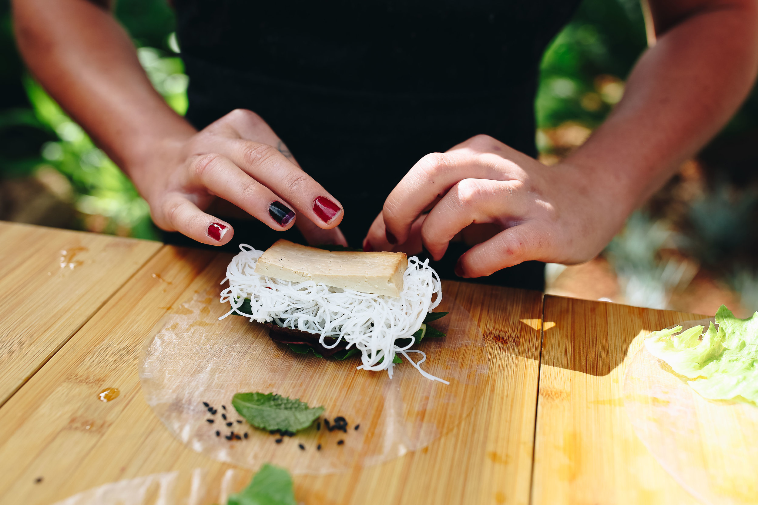 One of Julian's participants beginning to roll a perfectly portioned rice paper roll topped with rice noodles and smoked tofu.