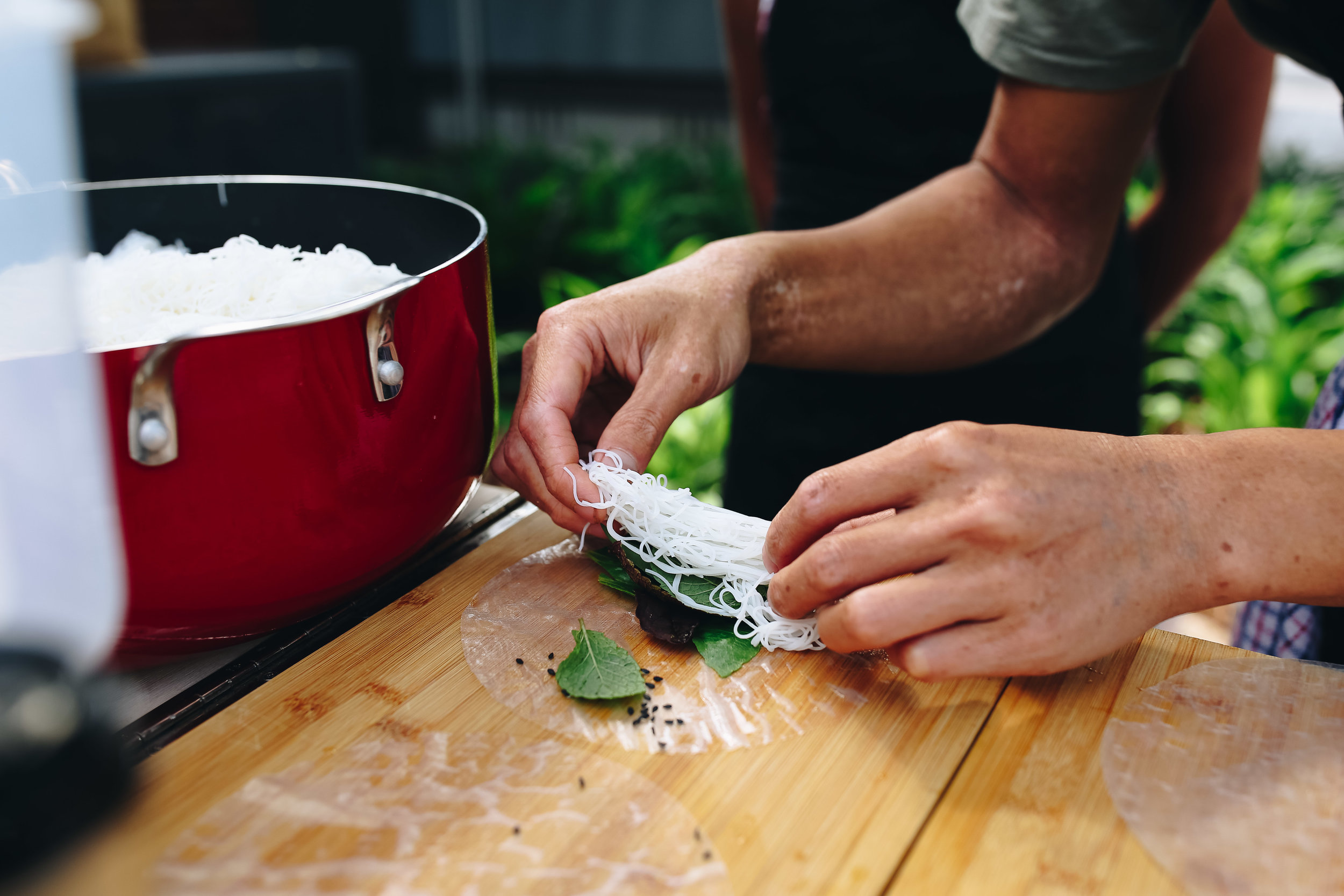 Julian delicately placing rice noodles into one of his rice paper rolls.