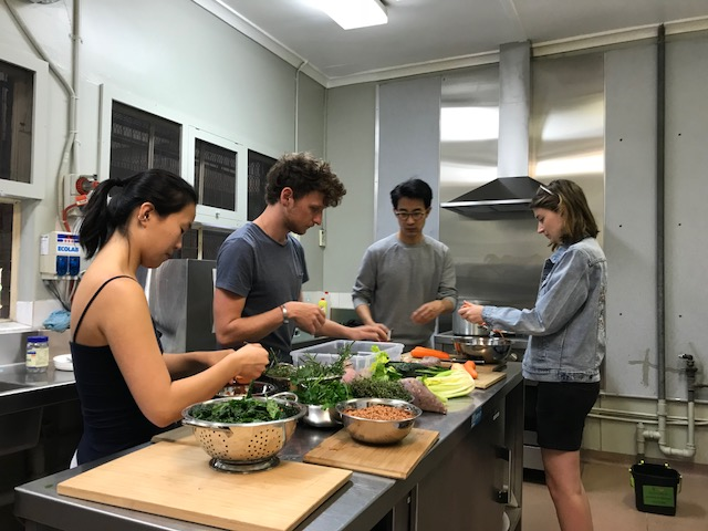The group in the Community Kitchen preparing a variety of herbs and vegetables in order to make the lentil soup.