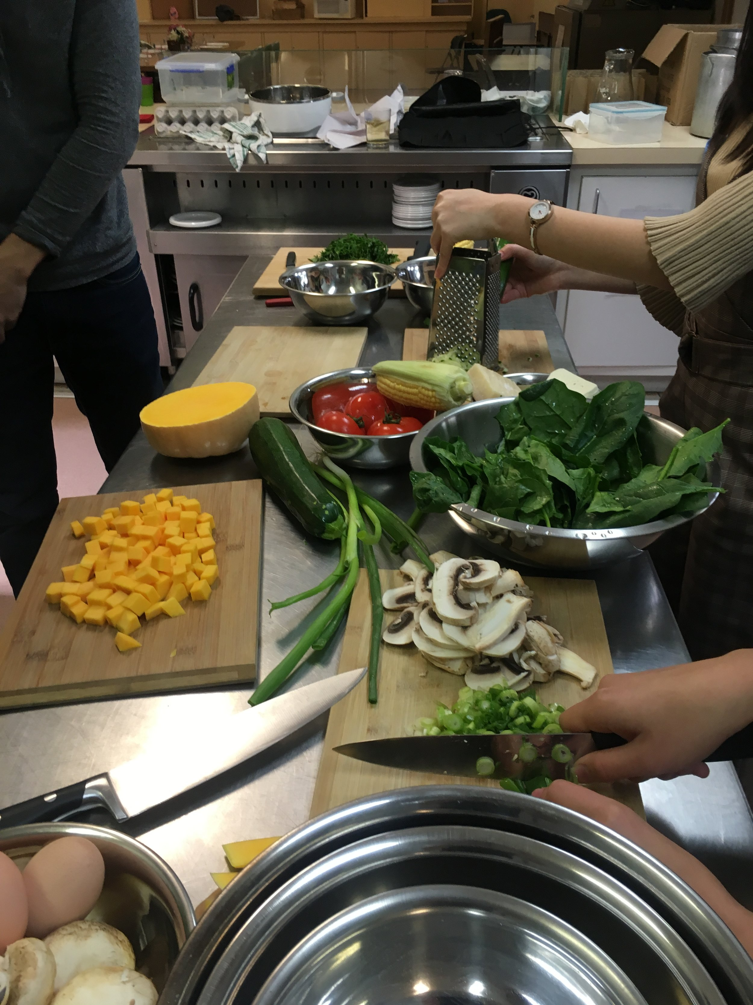 Several chopping boards with the group carefully processing spring onions, mushrooms, zucchini, pumpkin, spinach leaves, fresh corn and tomatoes.