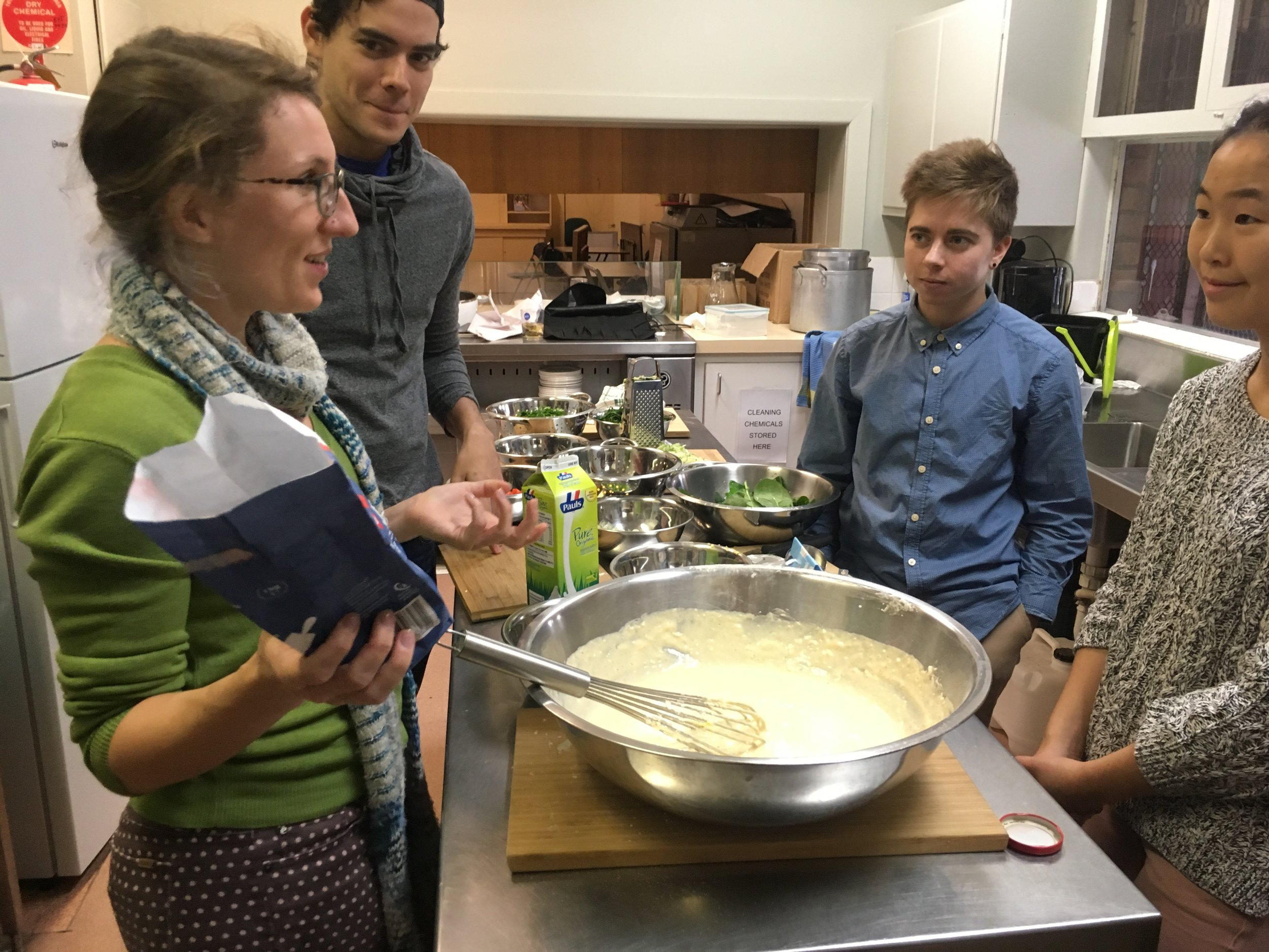 Jenn and the standing over a big bowl of pancake mix discussing how to get the perfect consistency.