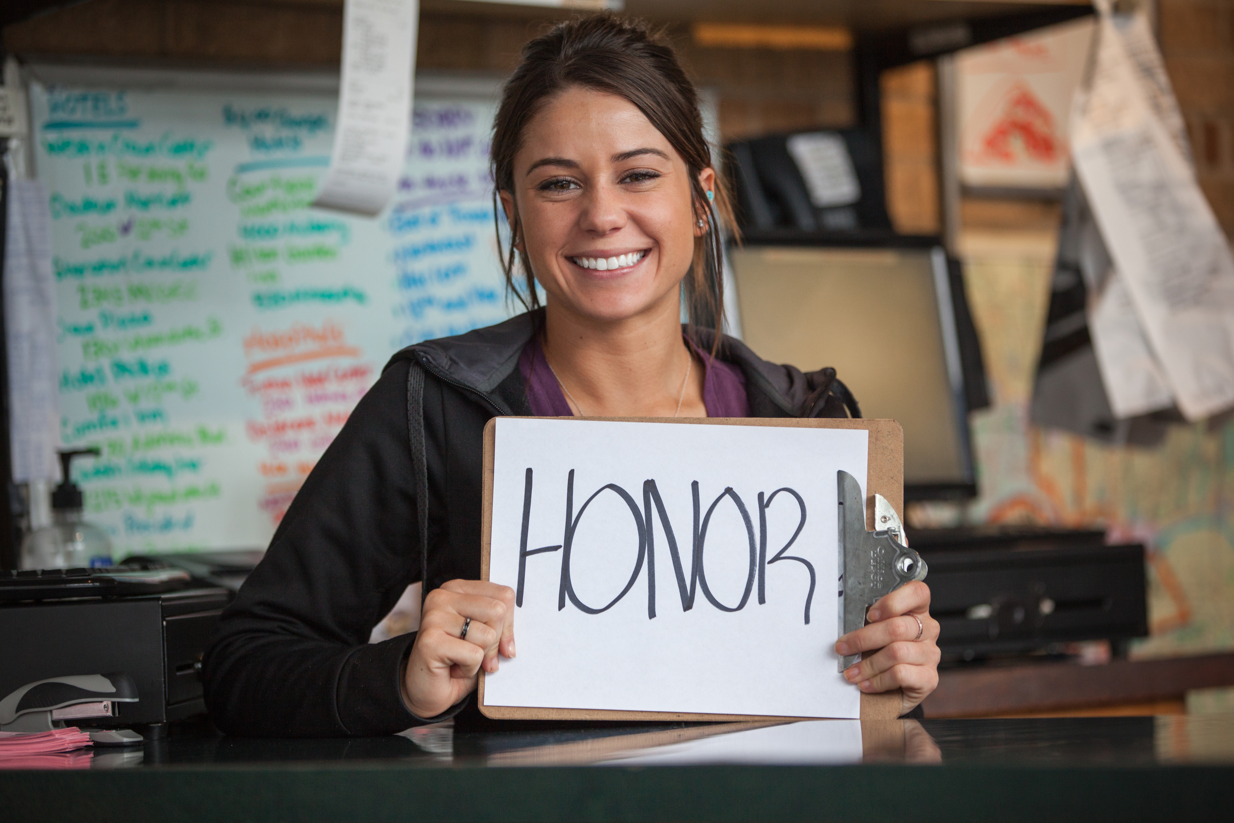 Young woman holding a sign saying honor.