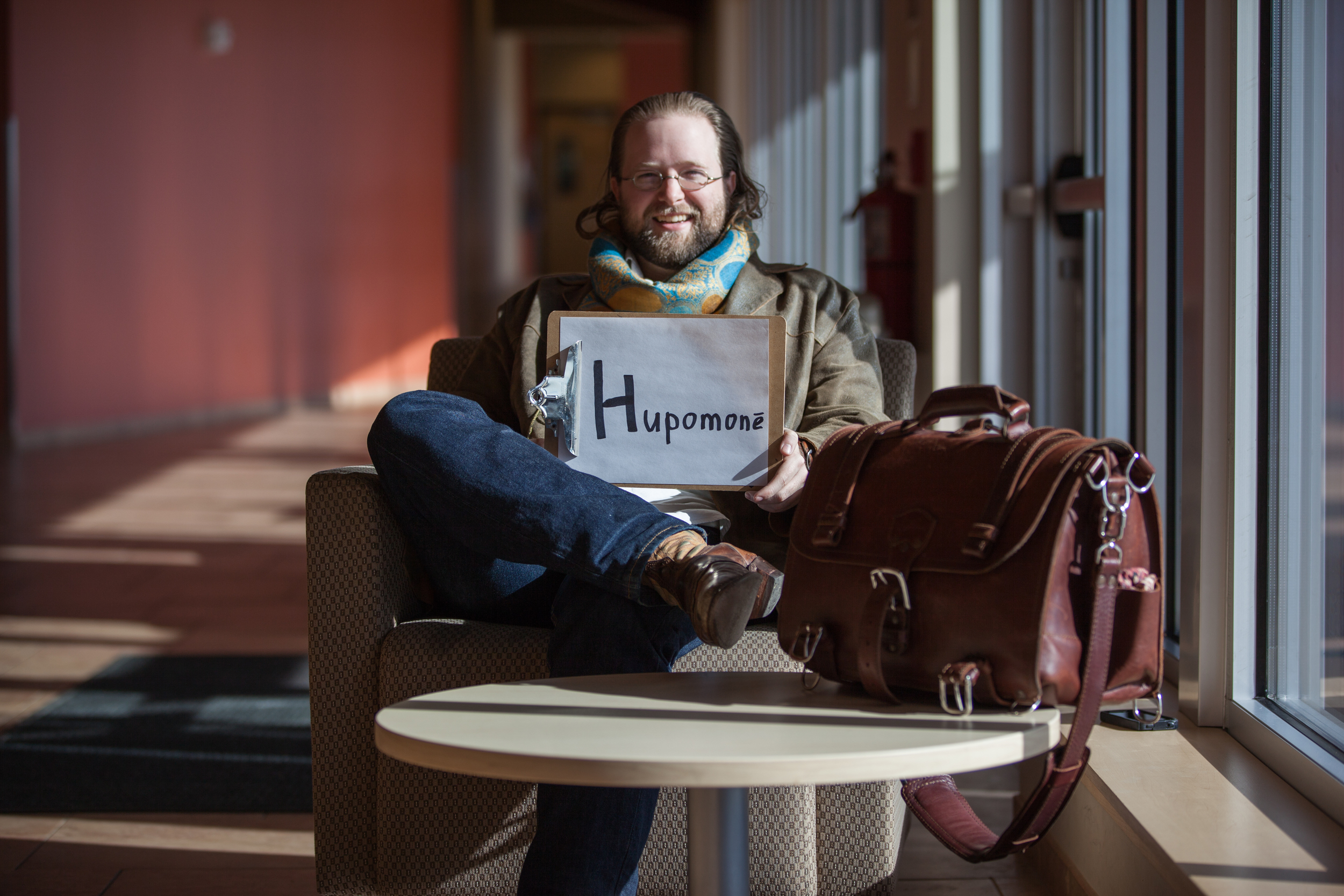 Man sitting in a chair holding a sign saying hupomone.