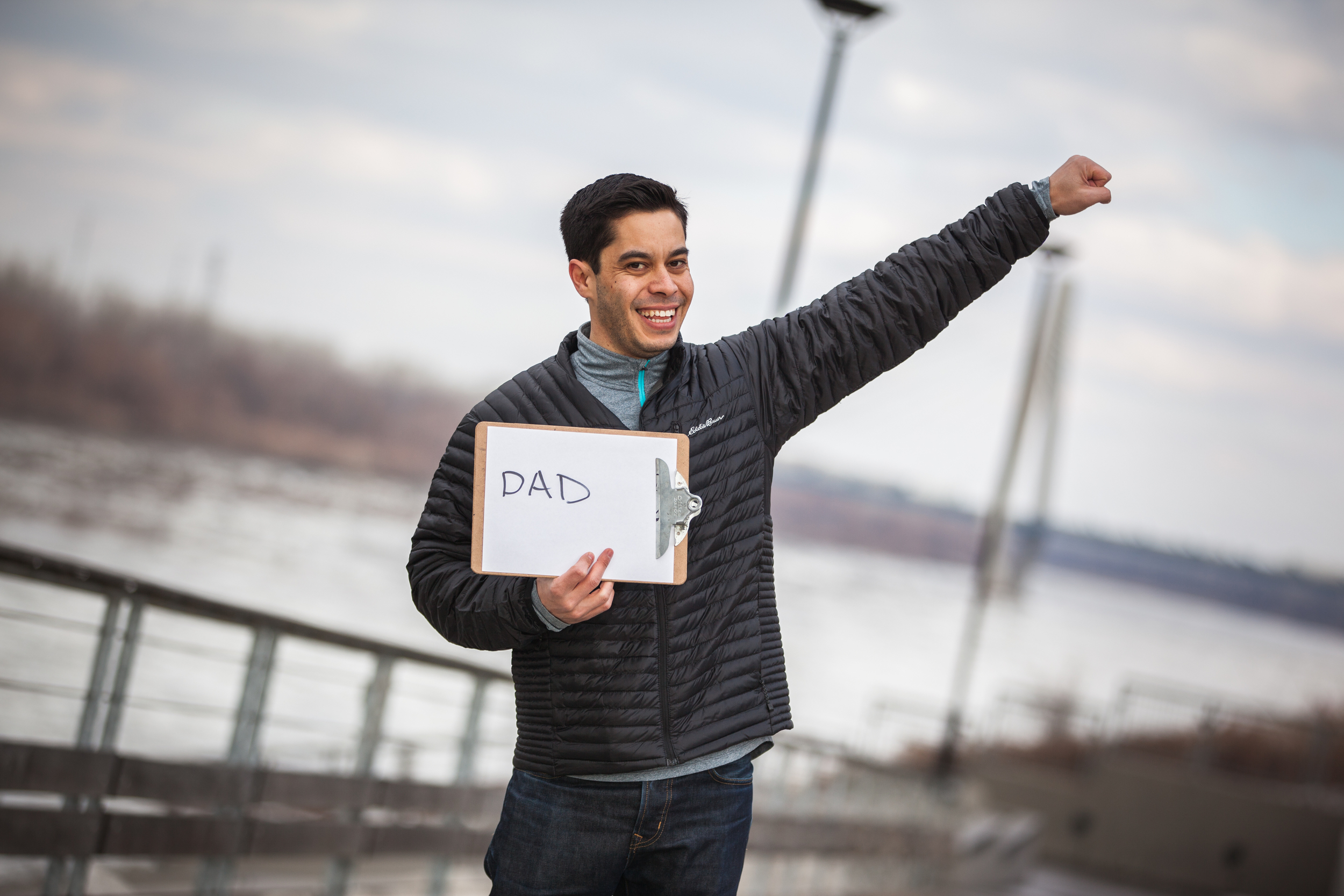 Man holding a sign saying dad.