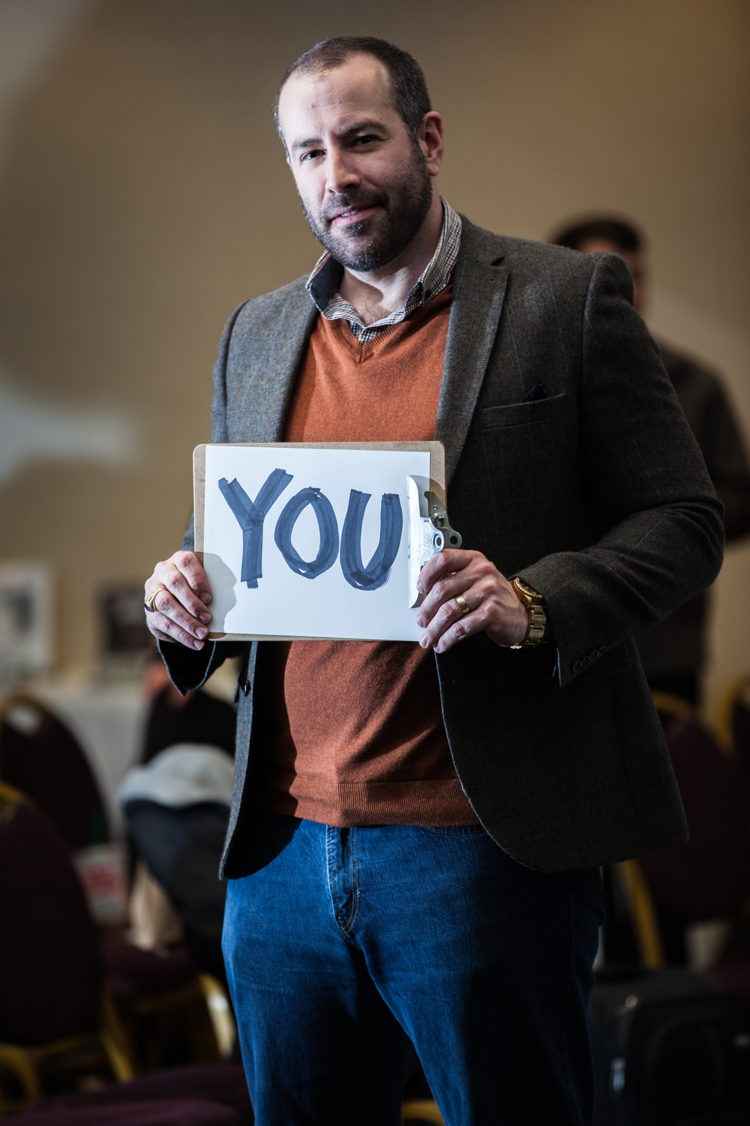 Man holding a sign saying you.