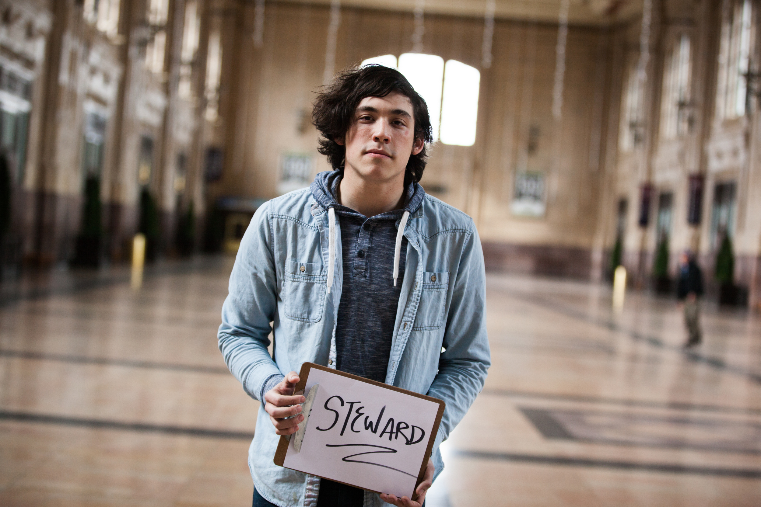 Young man holding a sign saying steward.