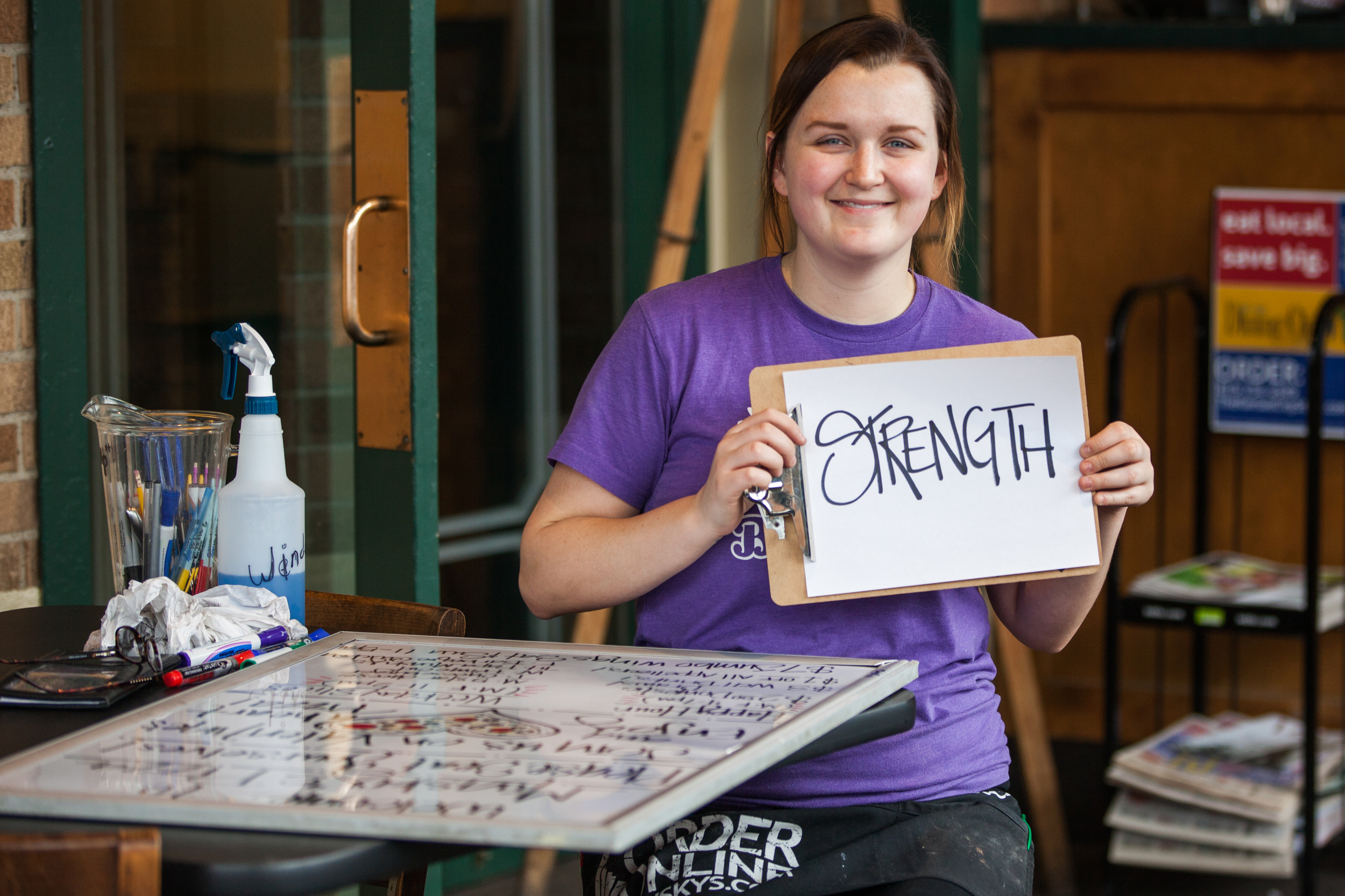 Young woman holding a sign saying strength.