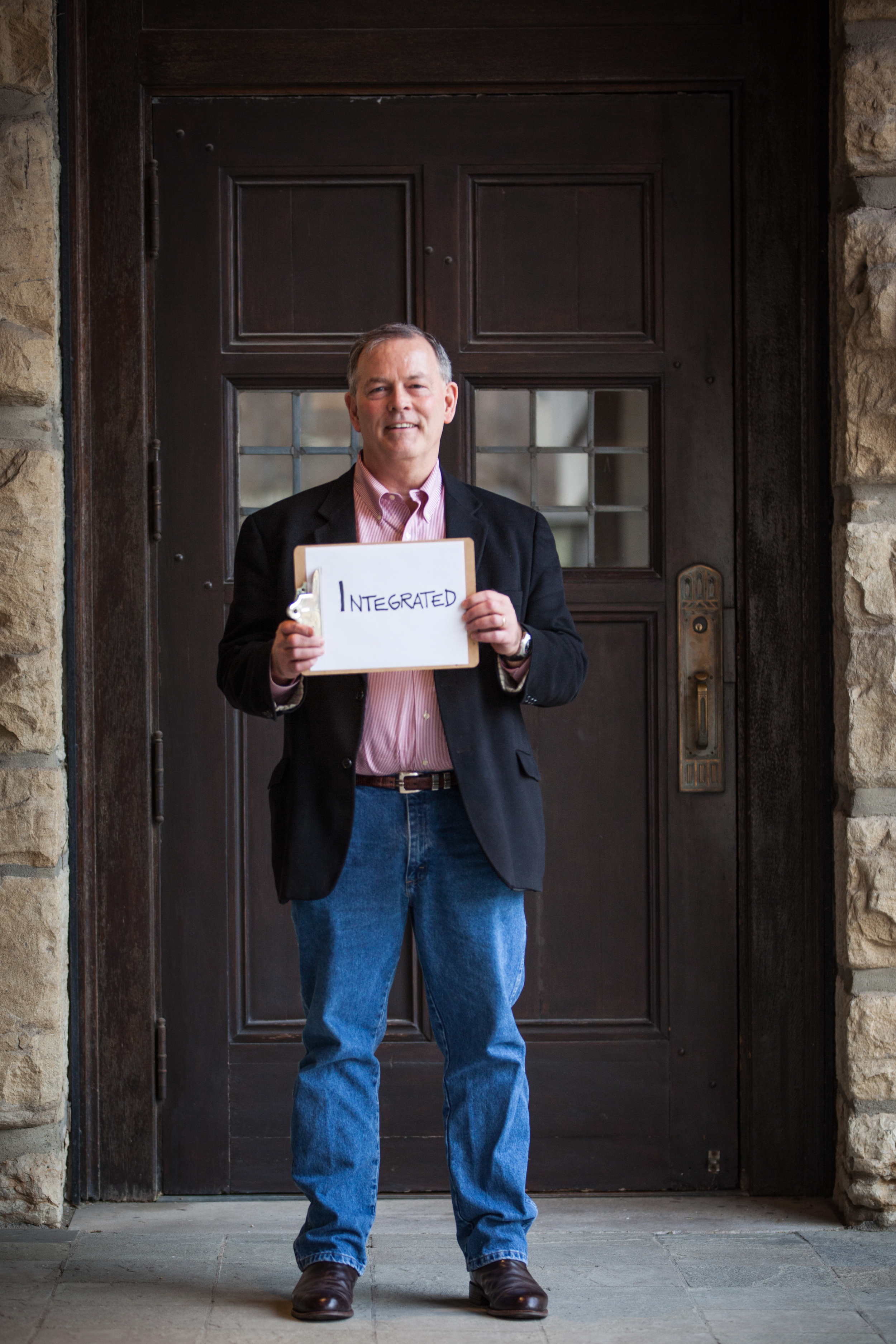 Man holding a sign saying integrated.