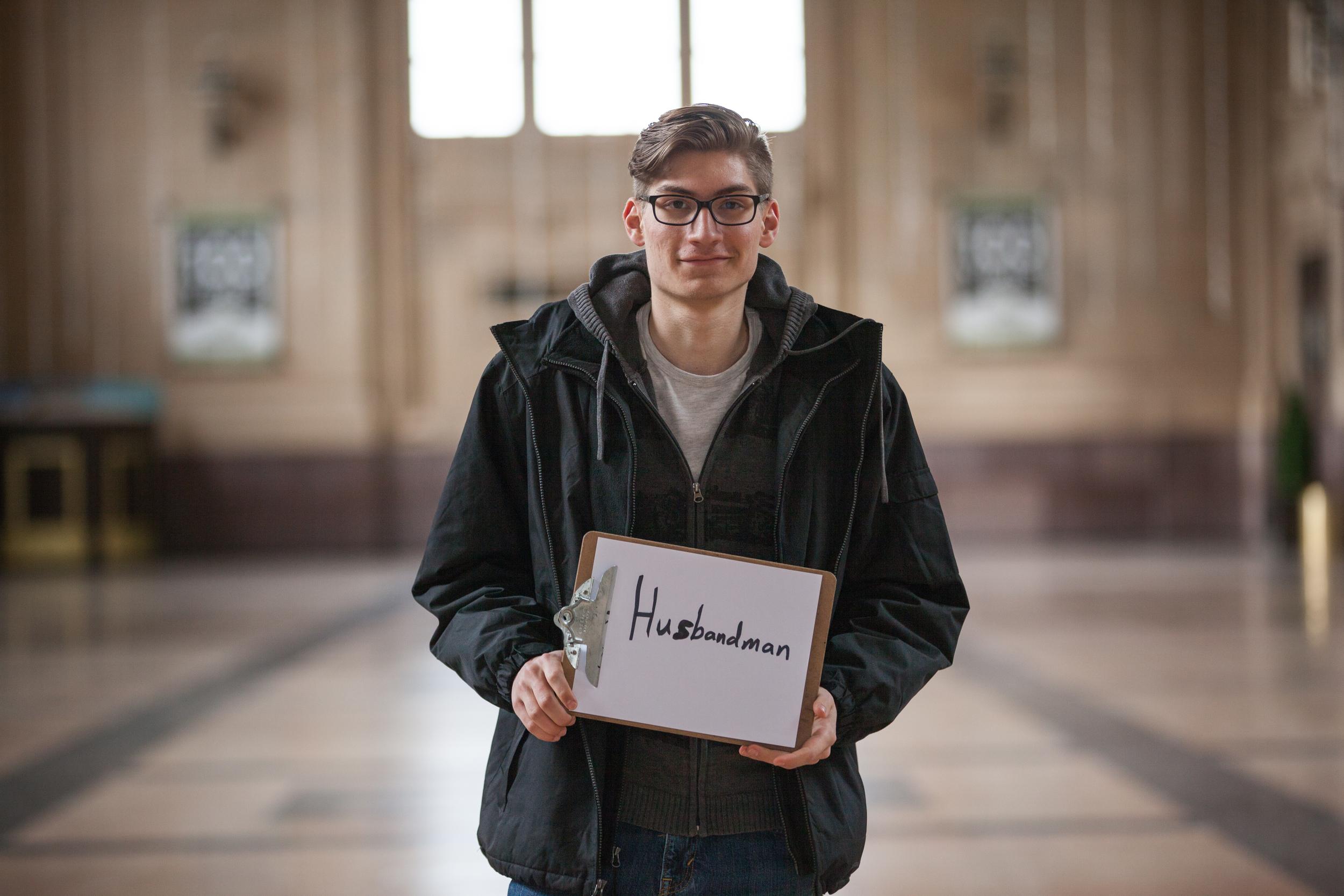 Young man holding a sign saying husbandmen.