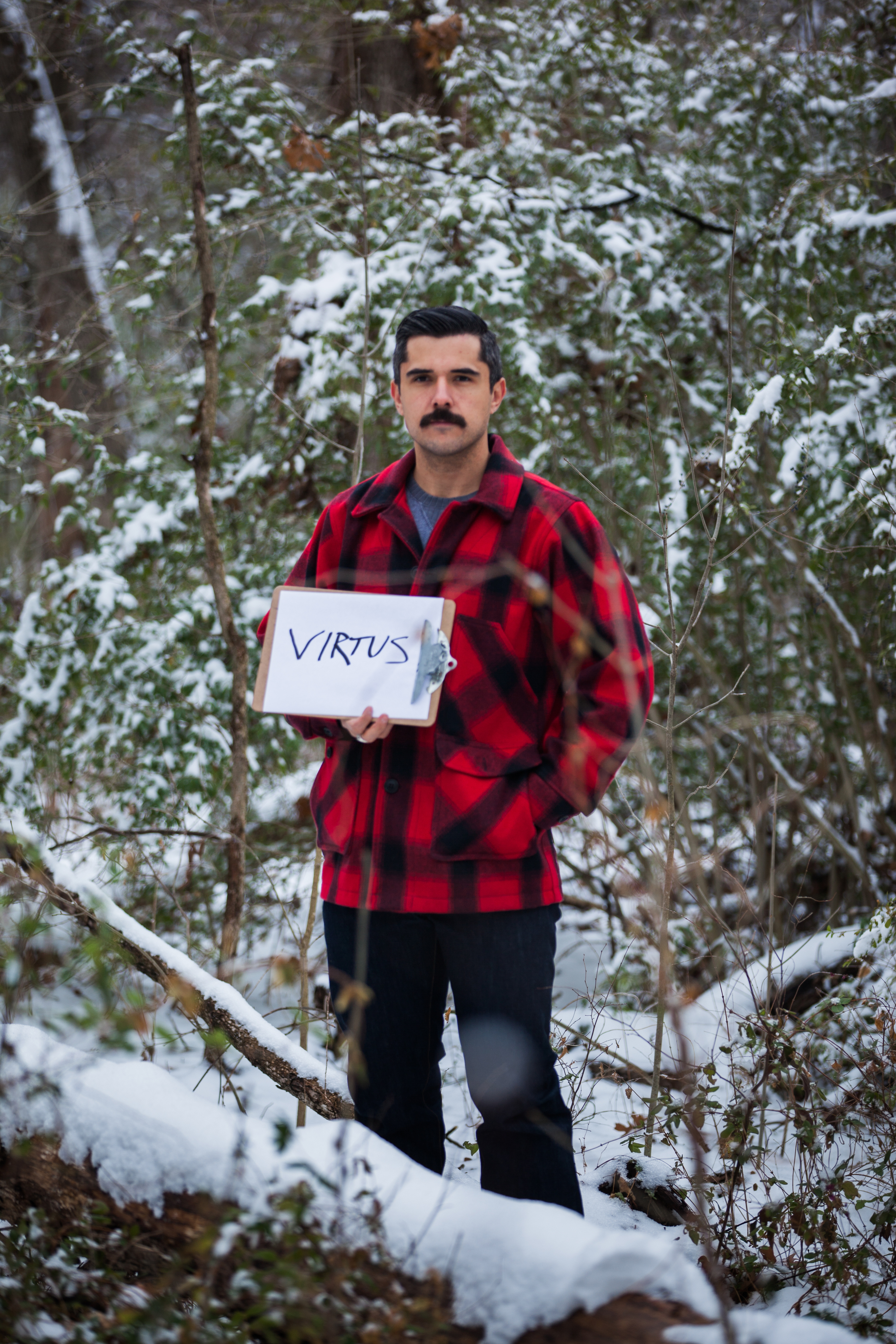 Man holding a sign in a snowy forrest with the word virtus on it.
