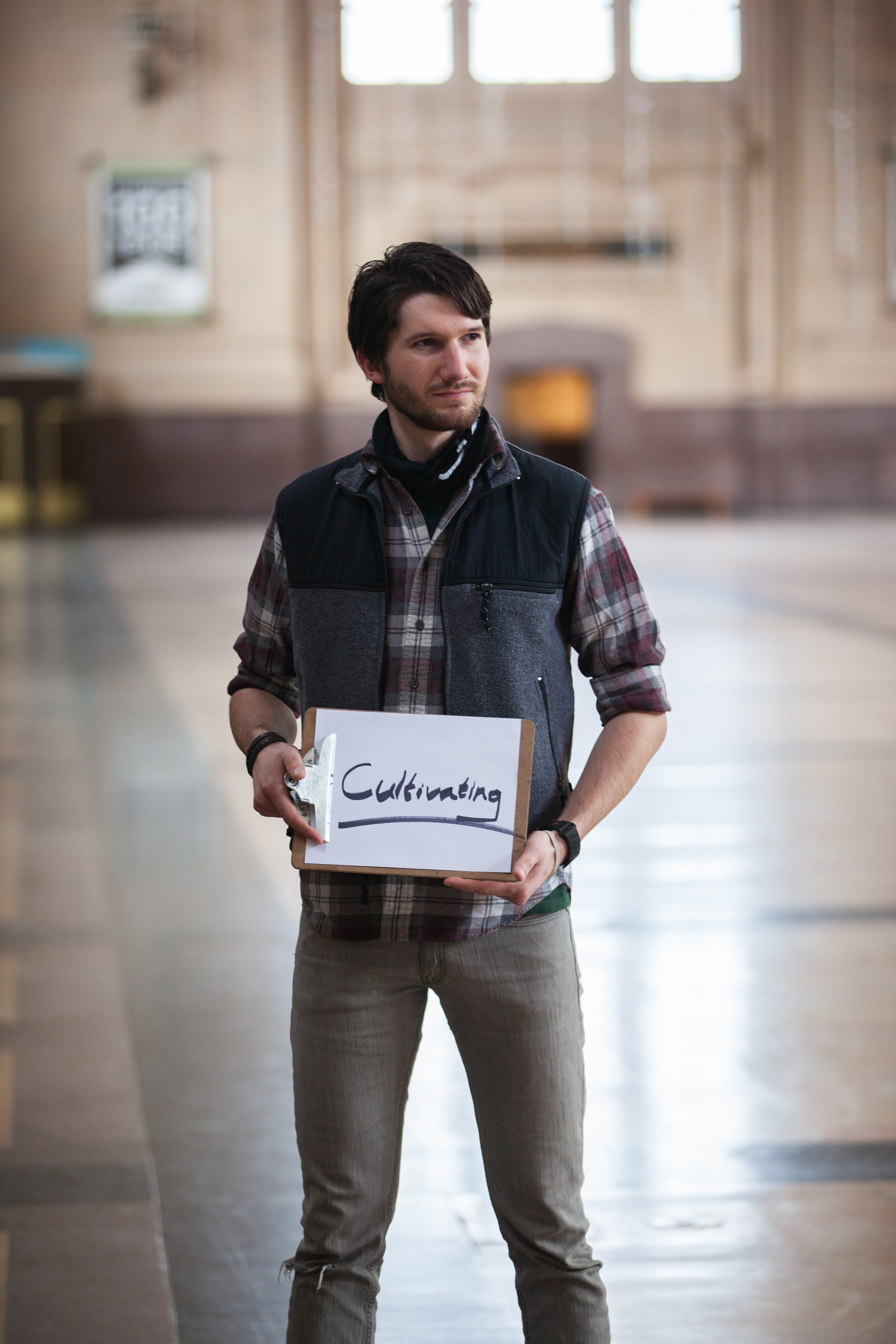 Man standing holding a sign saying of cultivating.