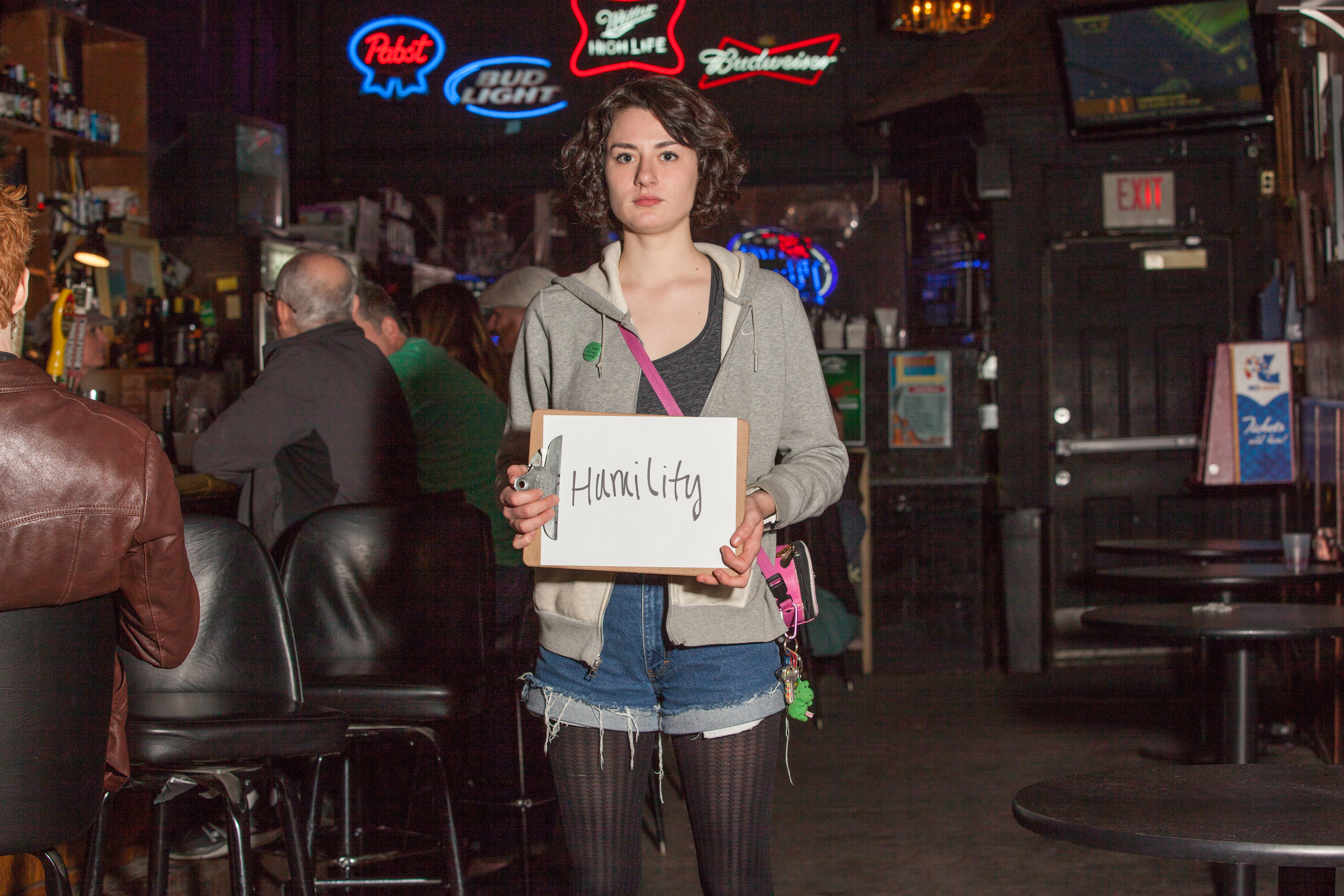 Woman holding a sign in a bar that says humility.