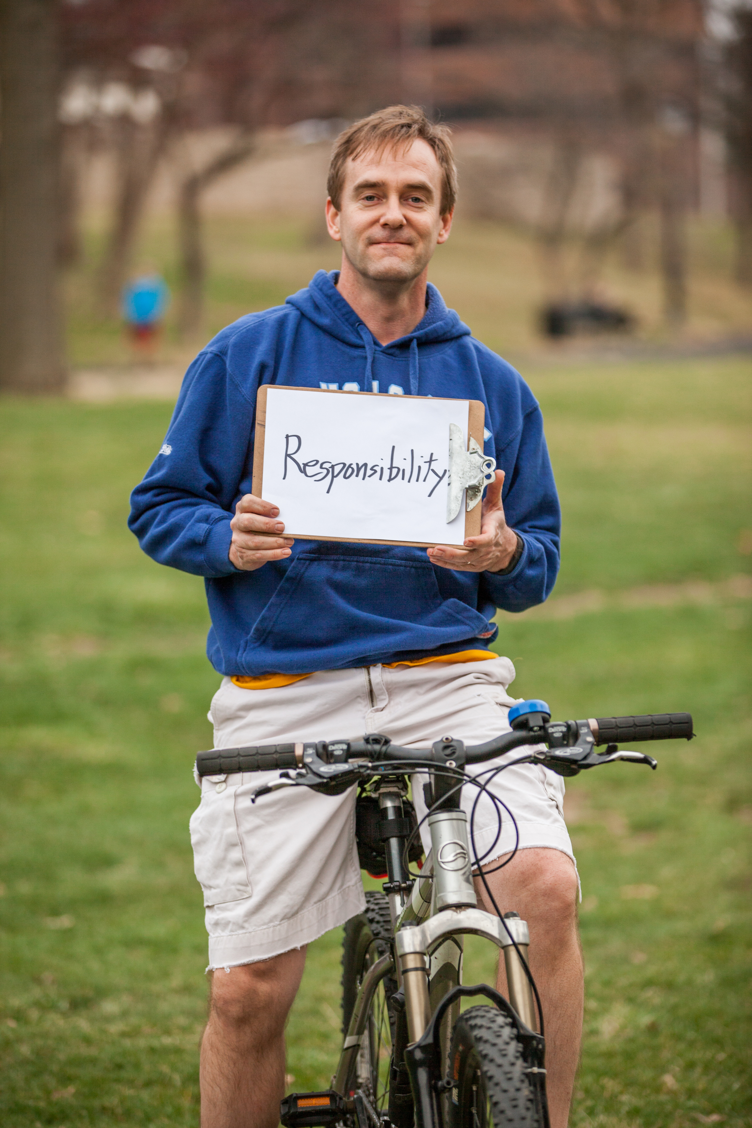Man on a bicycle holding a sign that says responsibility.