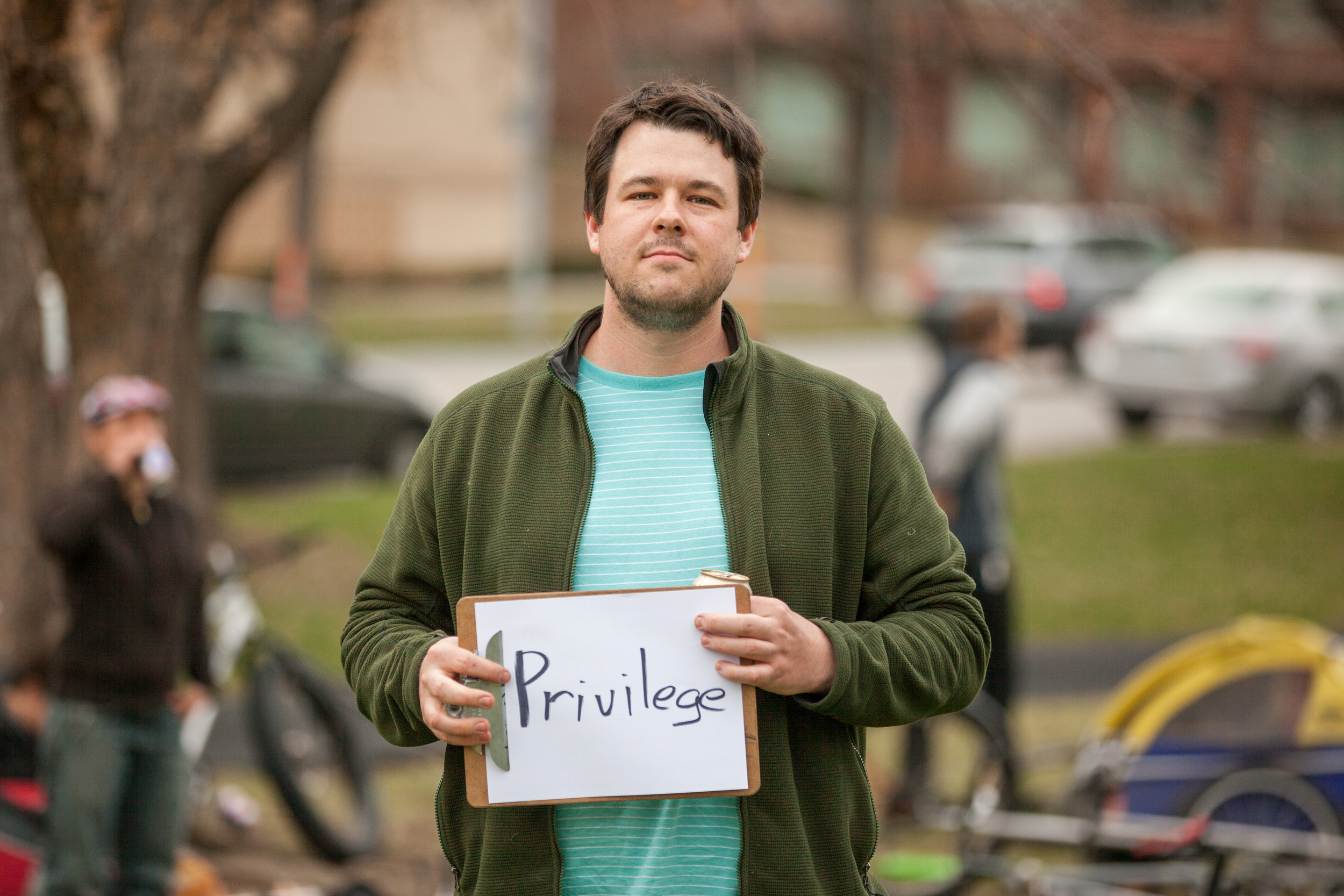 Man holding a sign saying privilege.