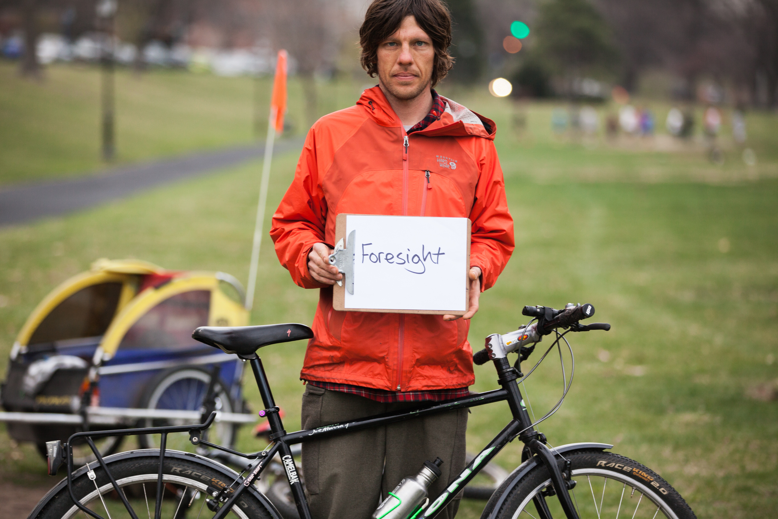 Man holding a sign saying foresight with his bicycle leaning against him.
