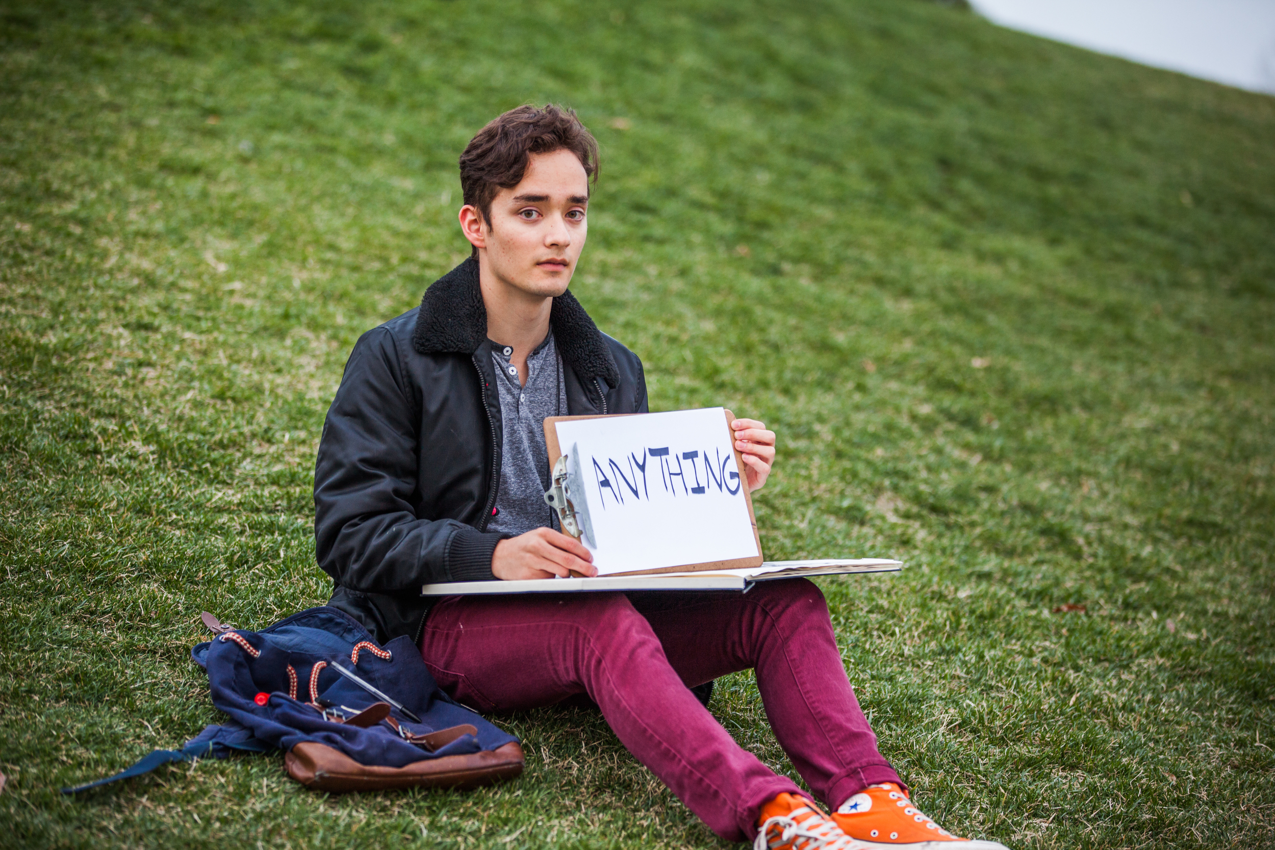 Young man sitting in the grass holding a sign saying anything.