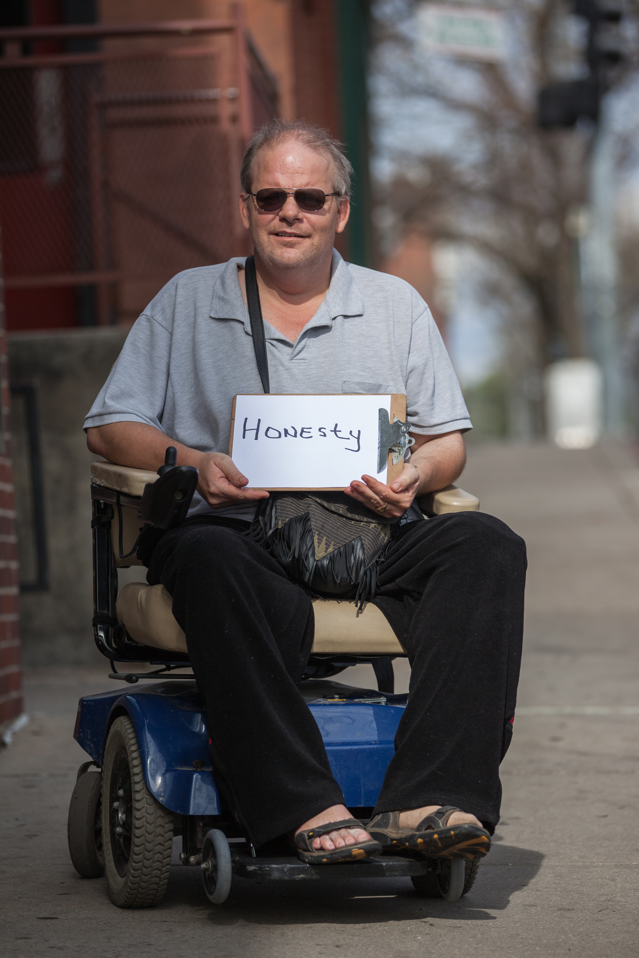 Man sitting a wheelchair holding a sign saying honesty.