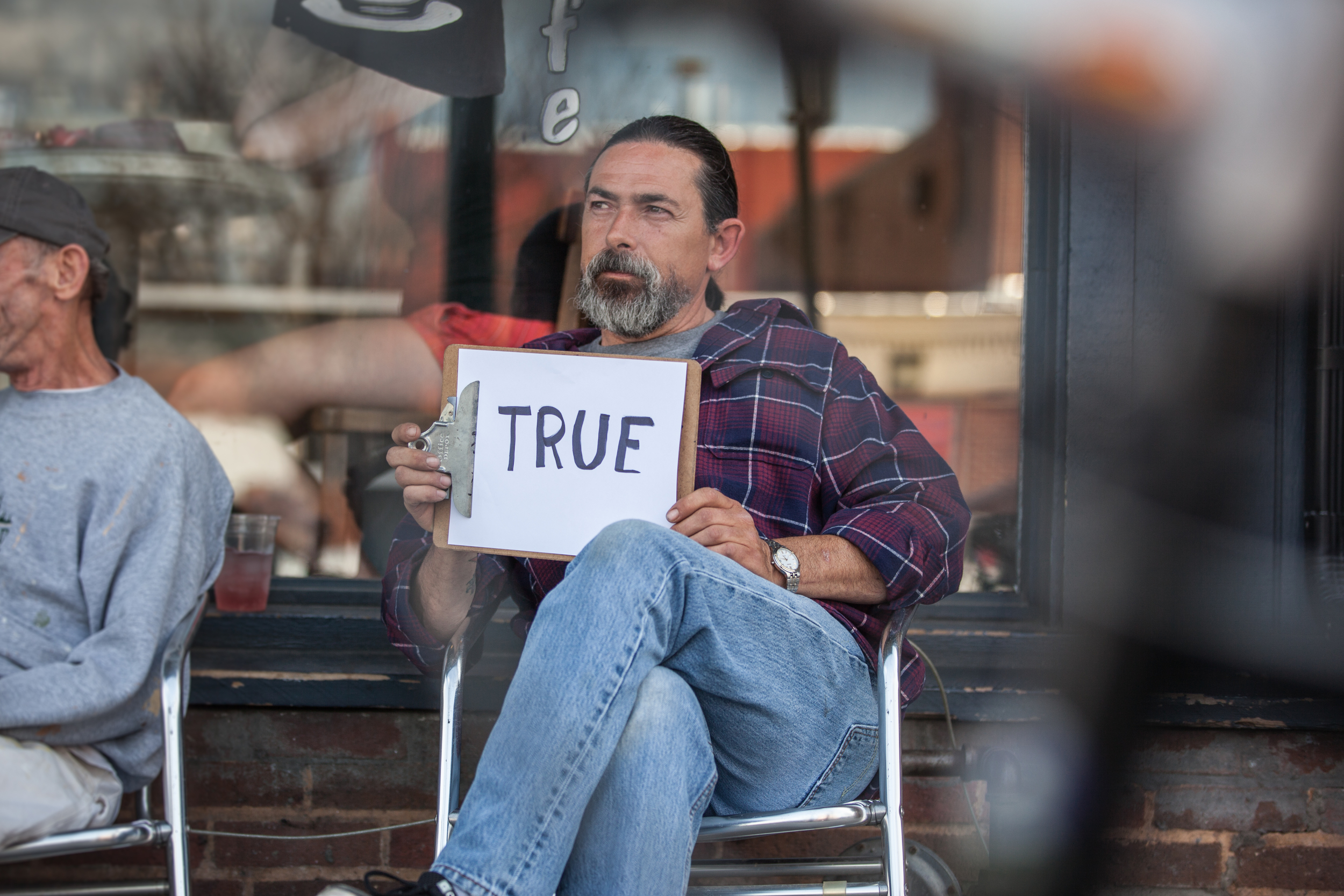 Man holding a sign that says true while sitting in a chair.