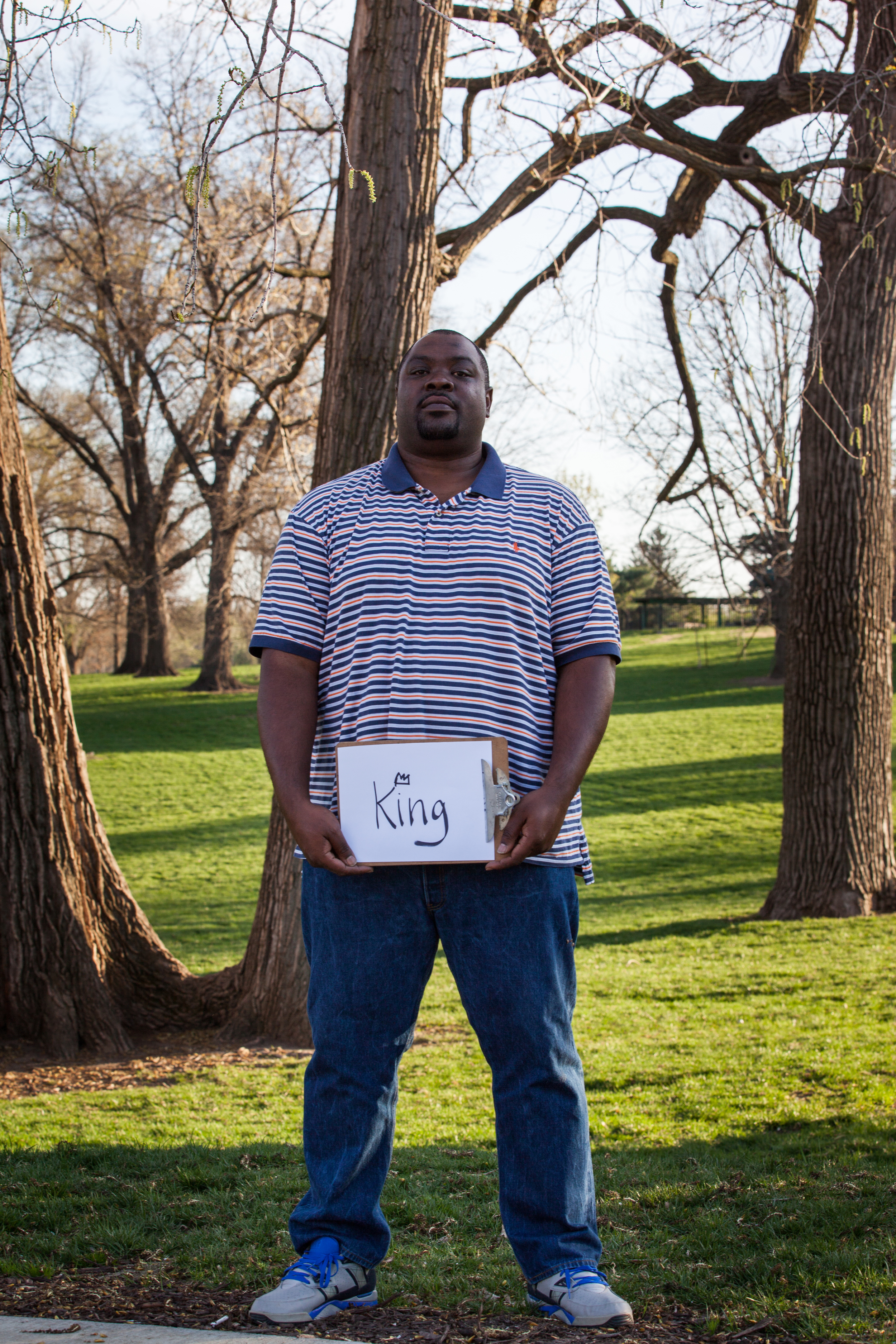 Man holding a sign that says king.