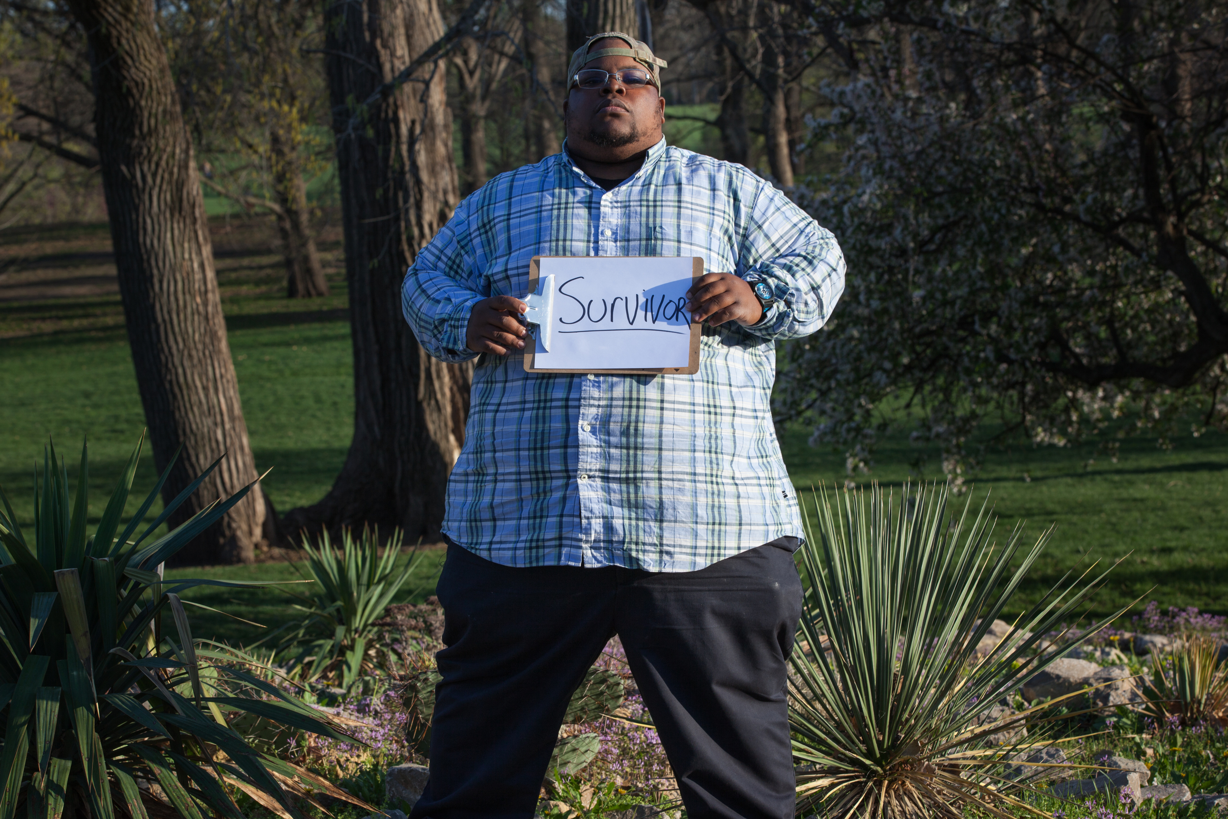 Man holding a sign that says survivor.