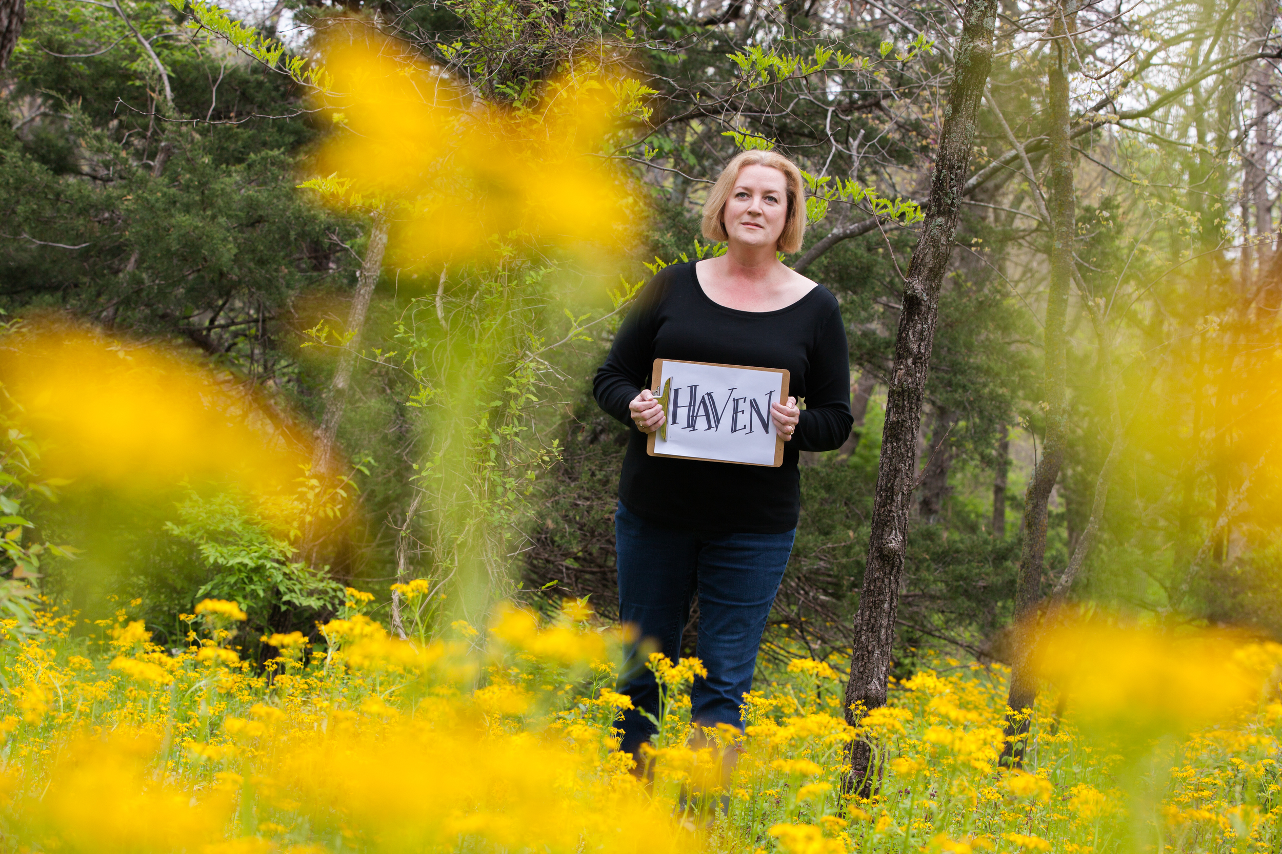 Woman holding a sign that says haven while standing in a field of flowers.