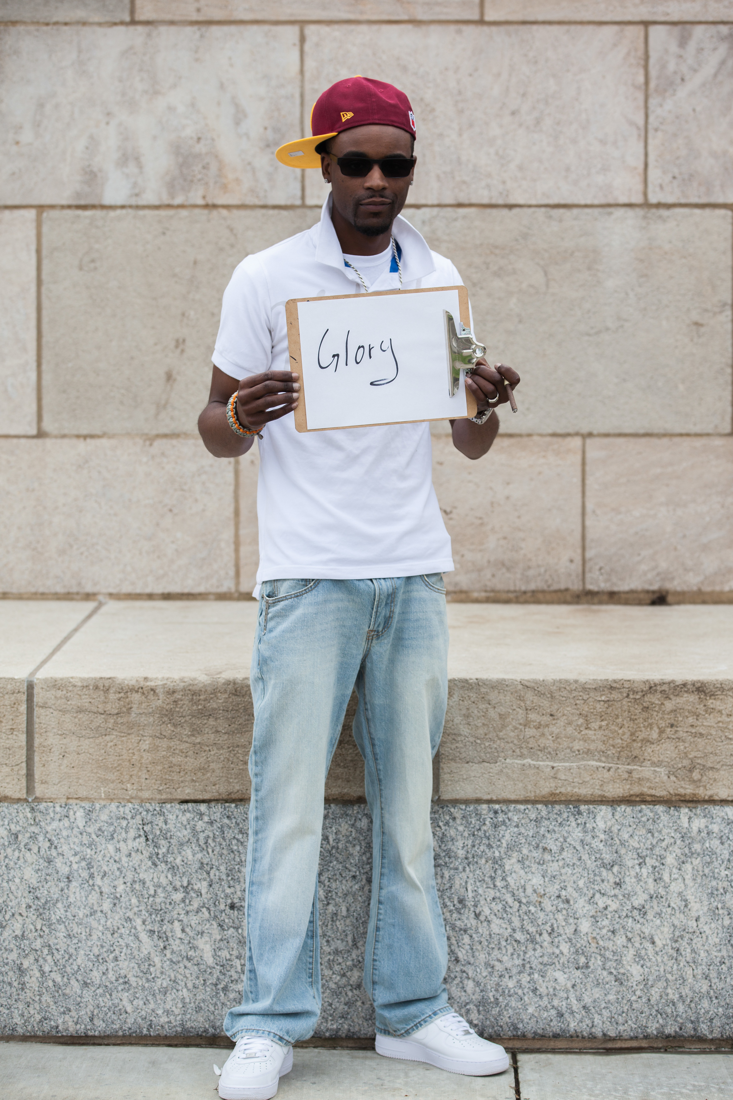 Man holding a sign that says glory.