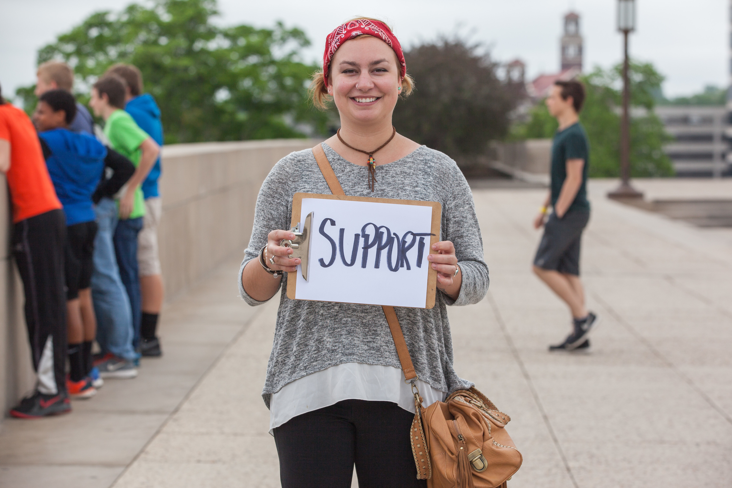 Young woman holding a sign that says support.