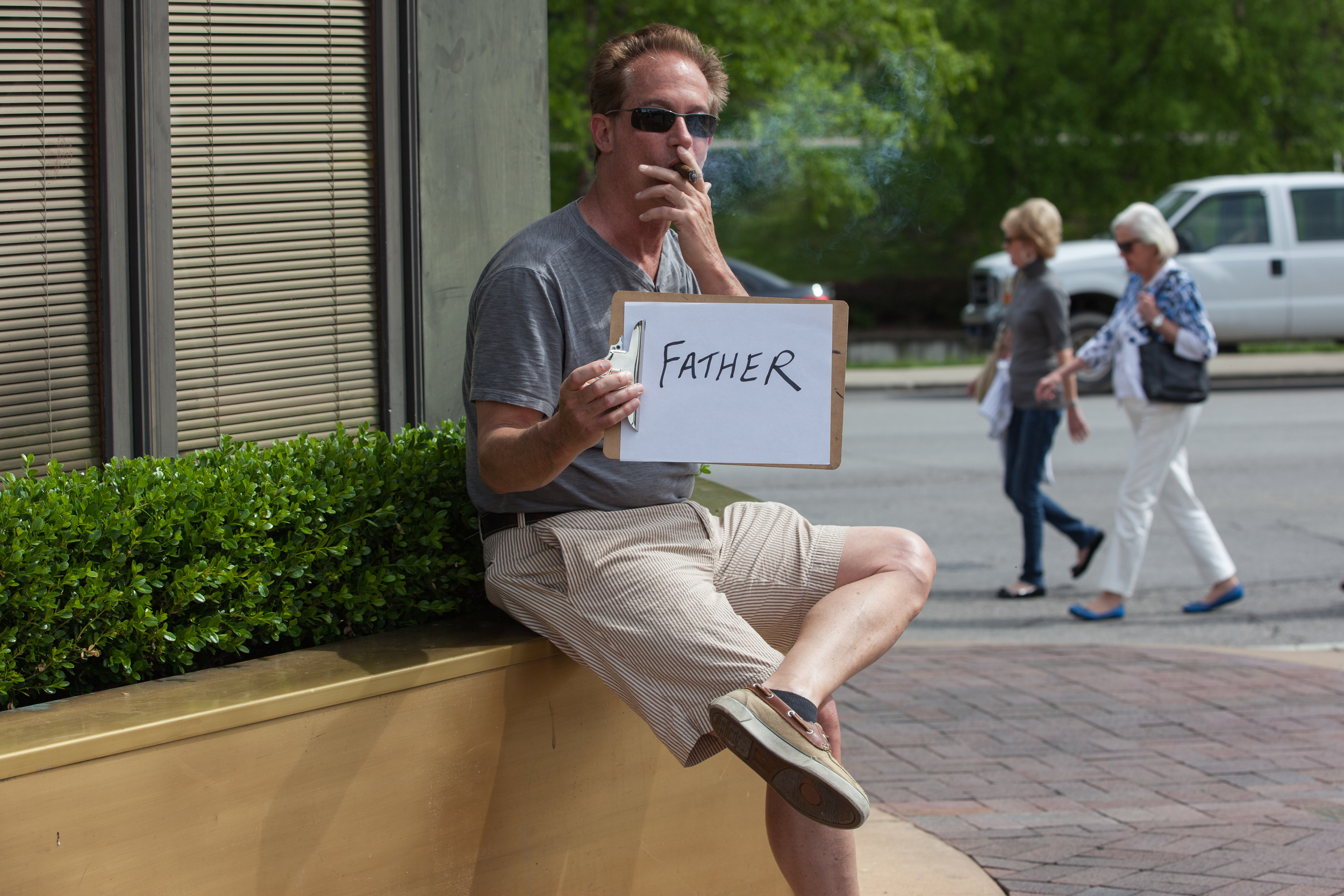 Man smoking a cigar while holding a sign that says father.