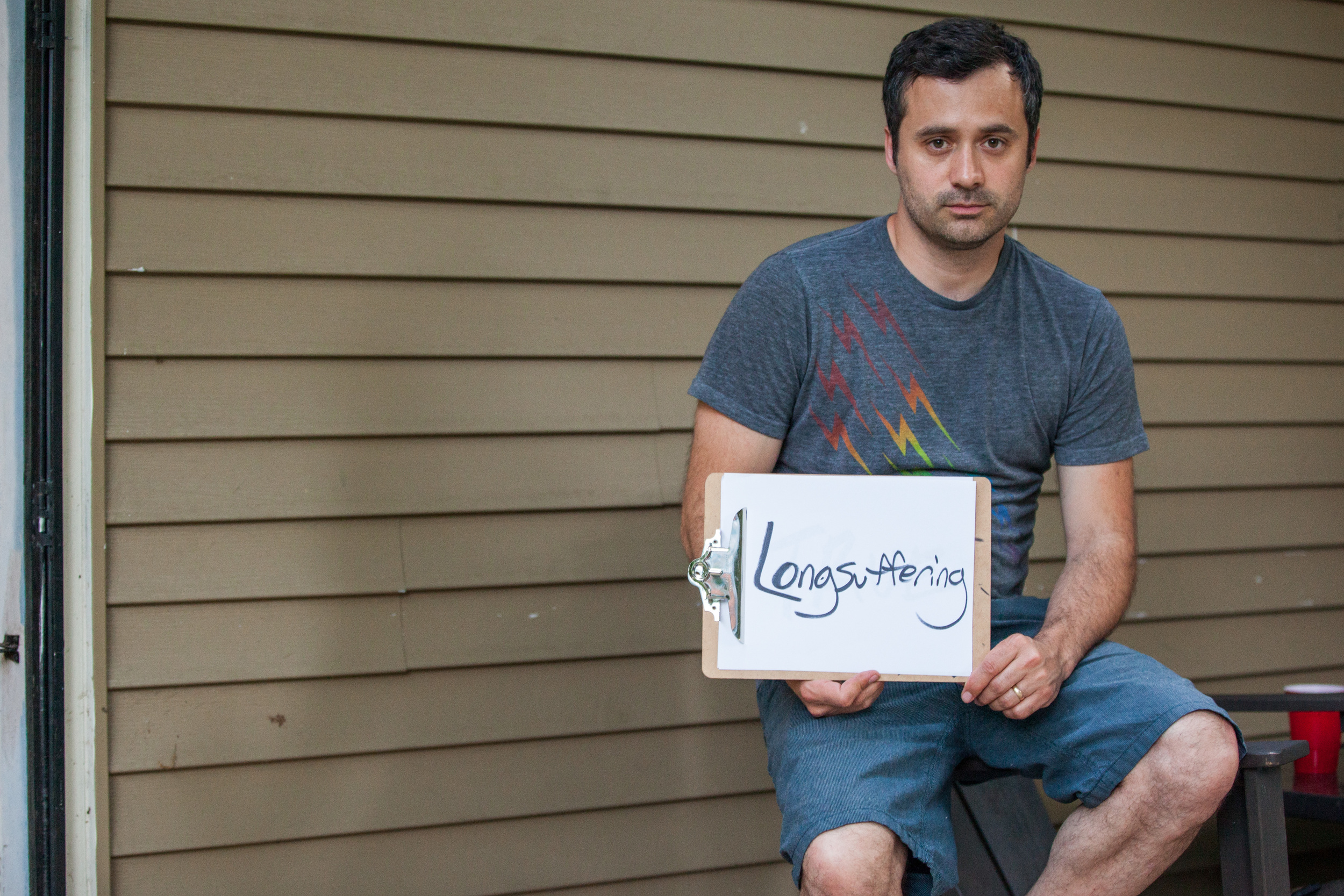 Man holding a sign that says long-suffering.