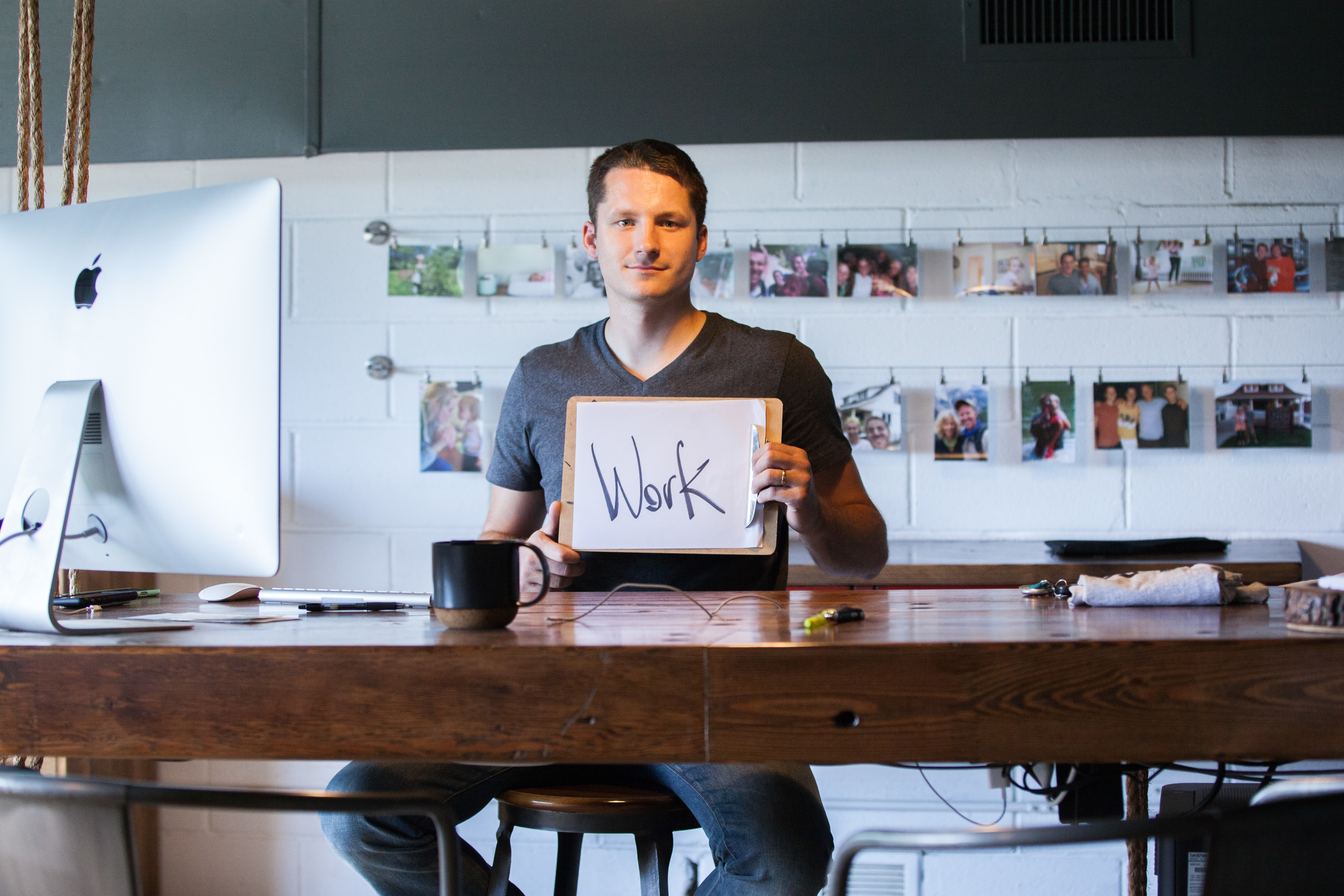 Man sitting at a desk holding a sign that says work.