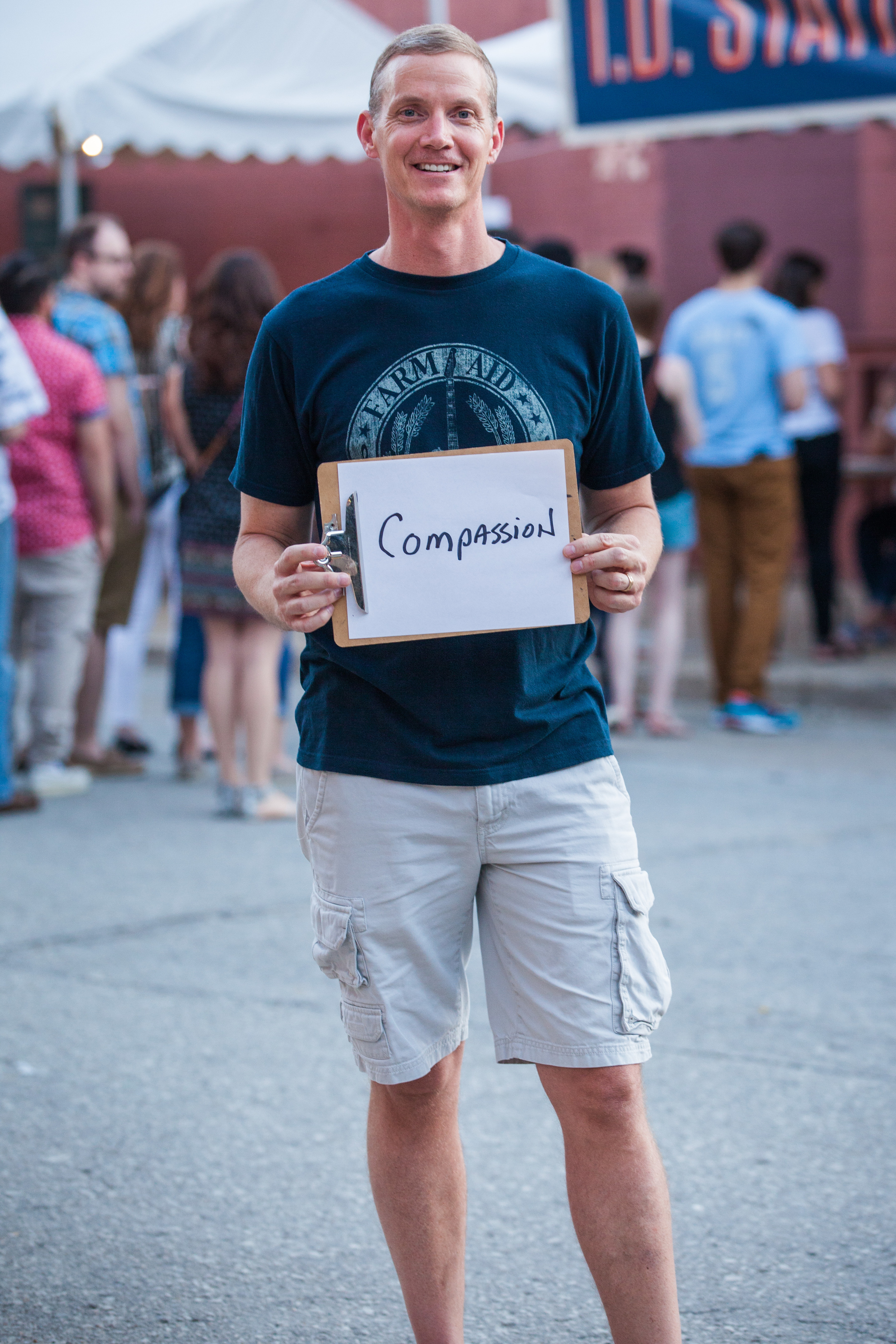 Man holding a sign that says compassion.