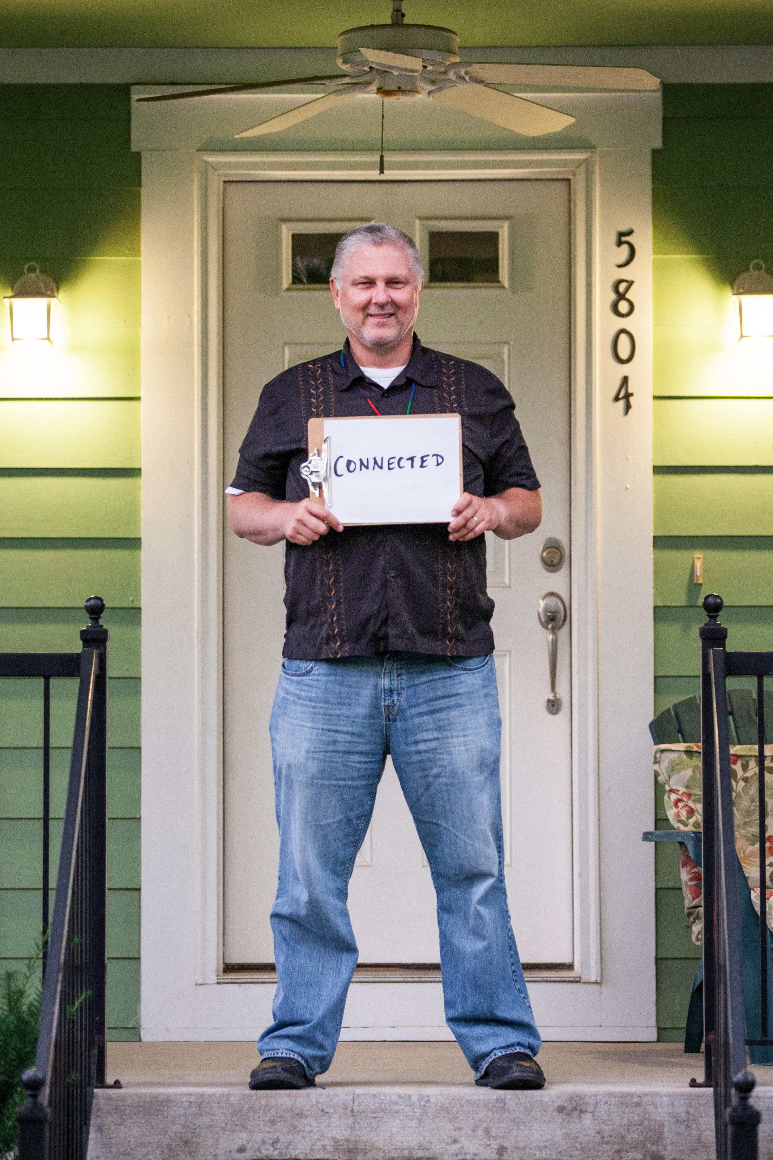 Man holding a  sign that says connected.