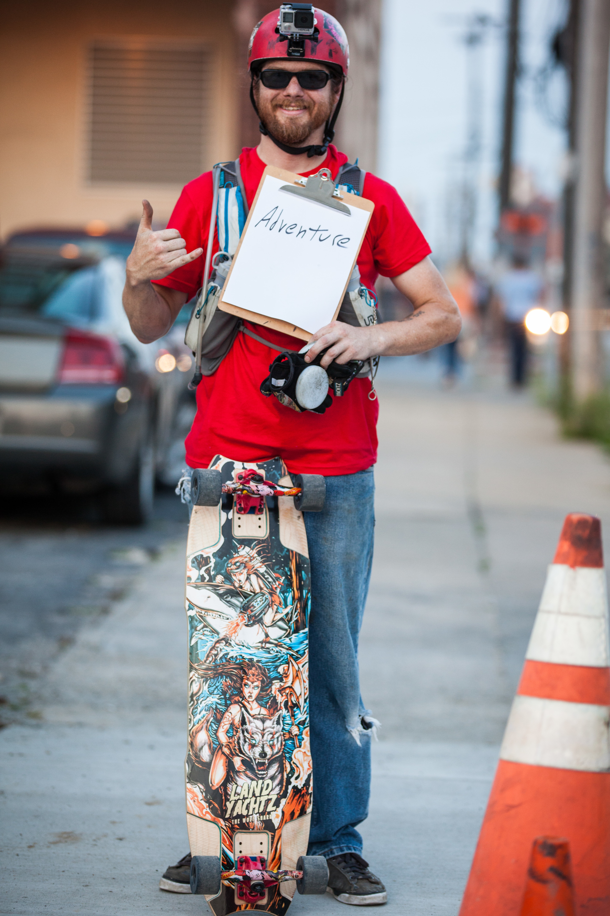 Man holding a sign that says adventure while a skateboard leans against him.