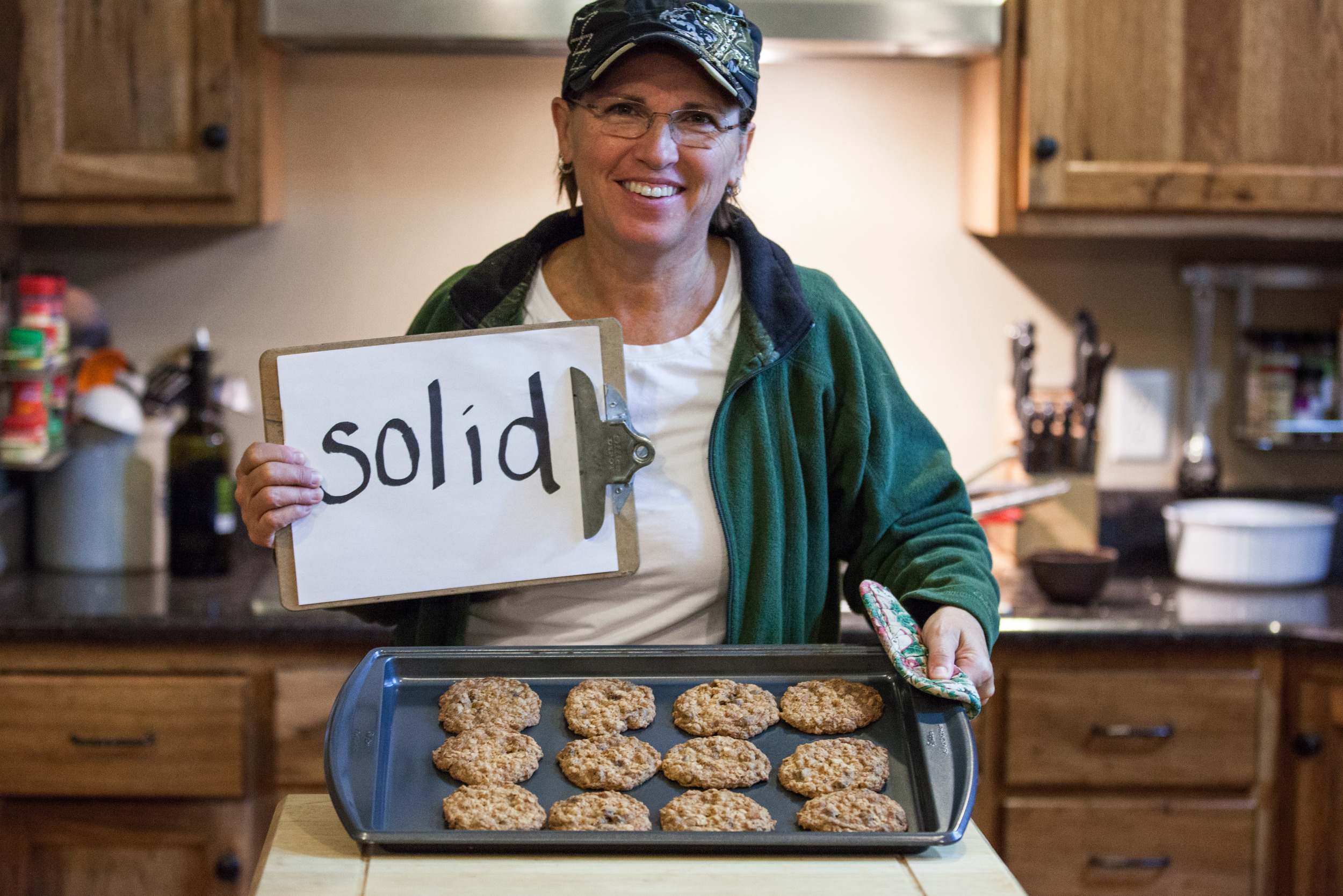 Woman holding a sign that says solid while also holding a pan of cookies.